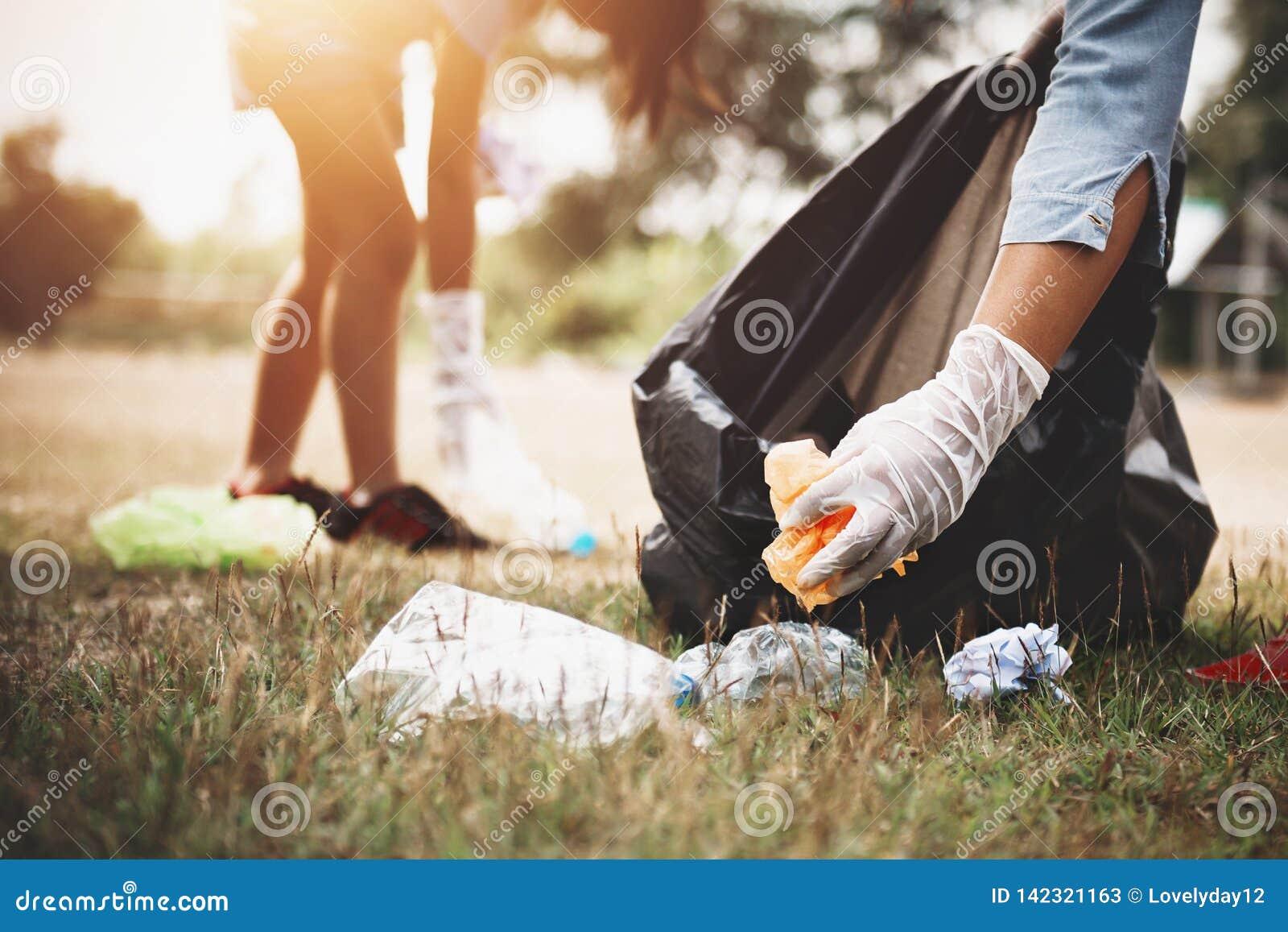 Frauenhand, die Abfallplastik für das Säubern aufhebt