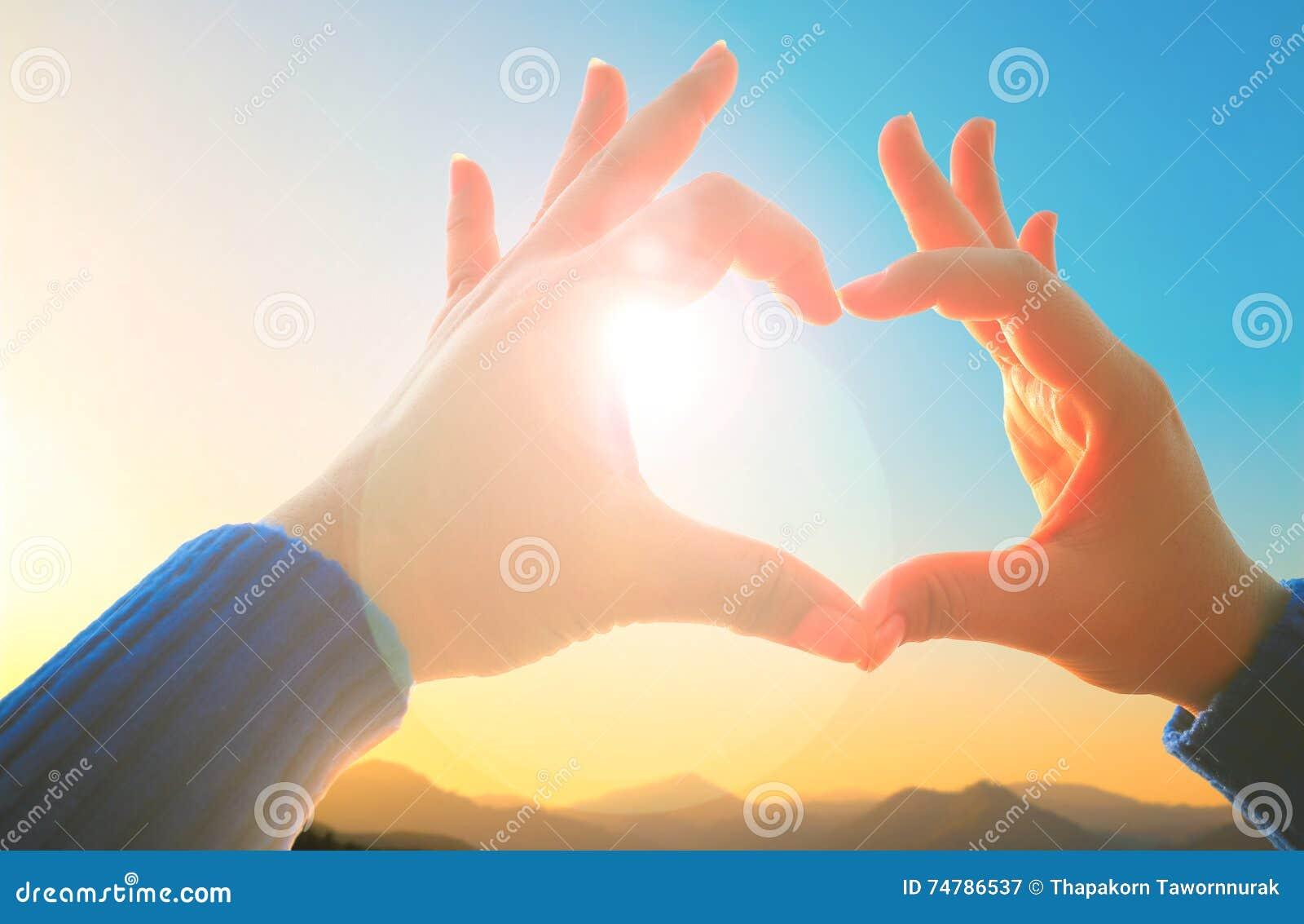 Frauenhand, die Liebeszeichen auf der Natur macht