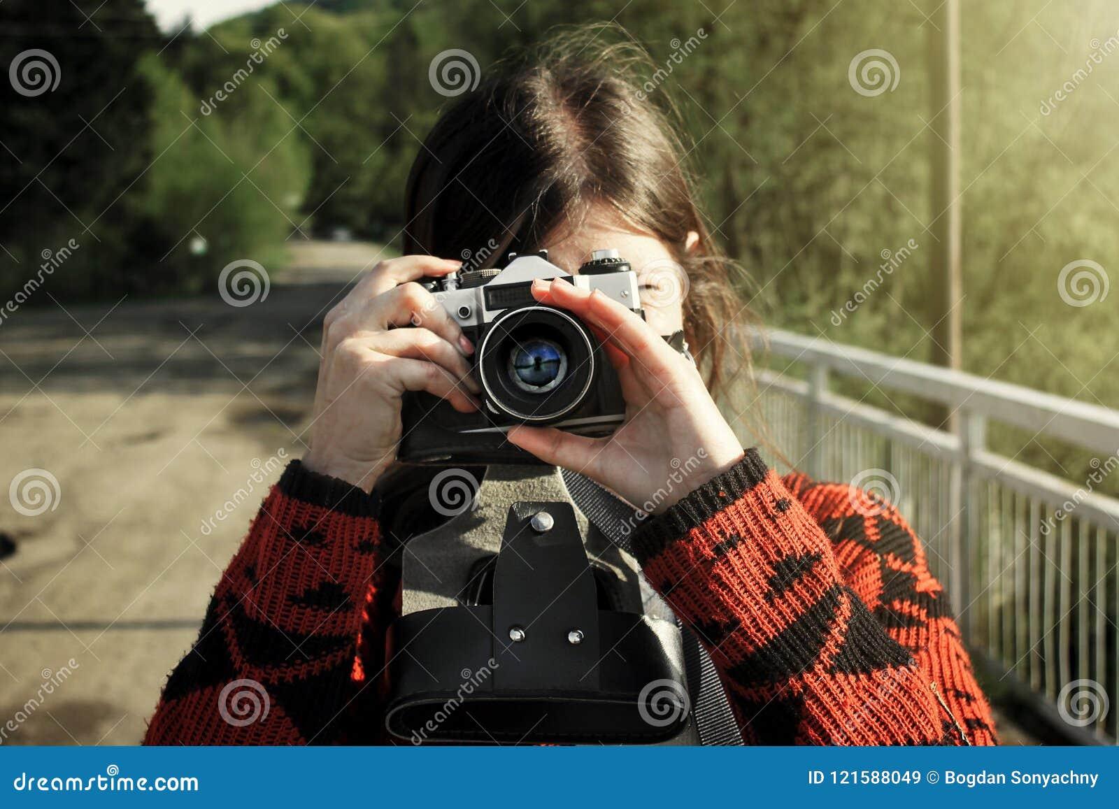 Frauenhippie-Reisender, der analoge Fotokamera in den Bergen hält,