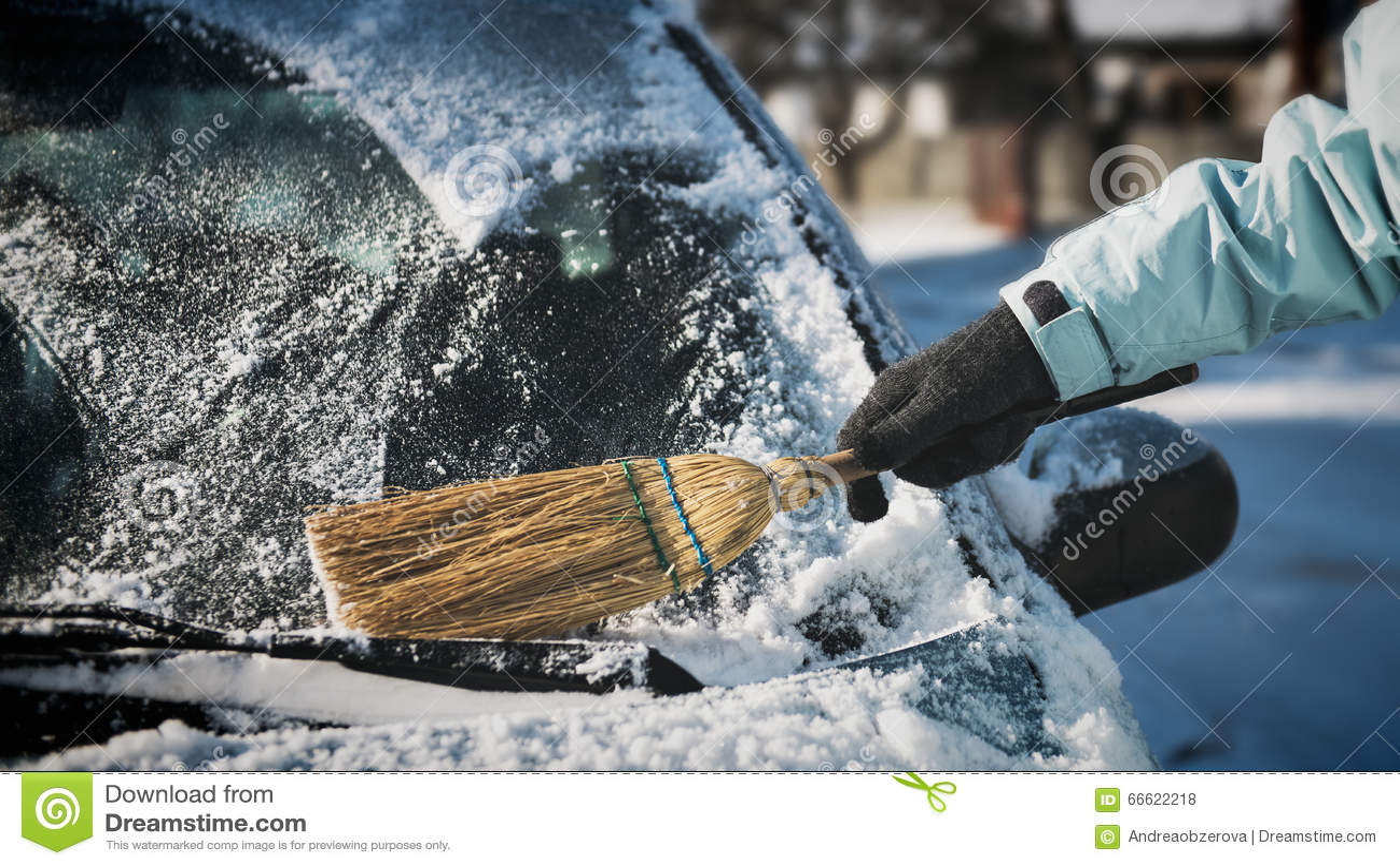 Frauenreinigungsschnee von ihrem Auto mit einem Besen