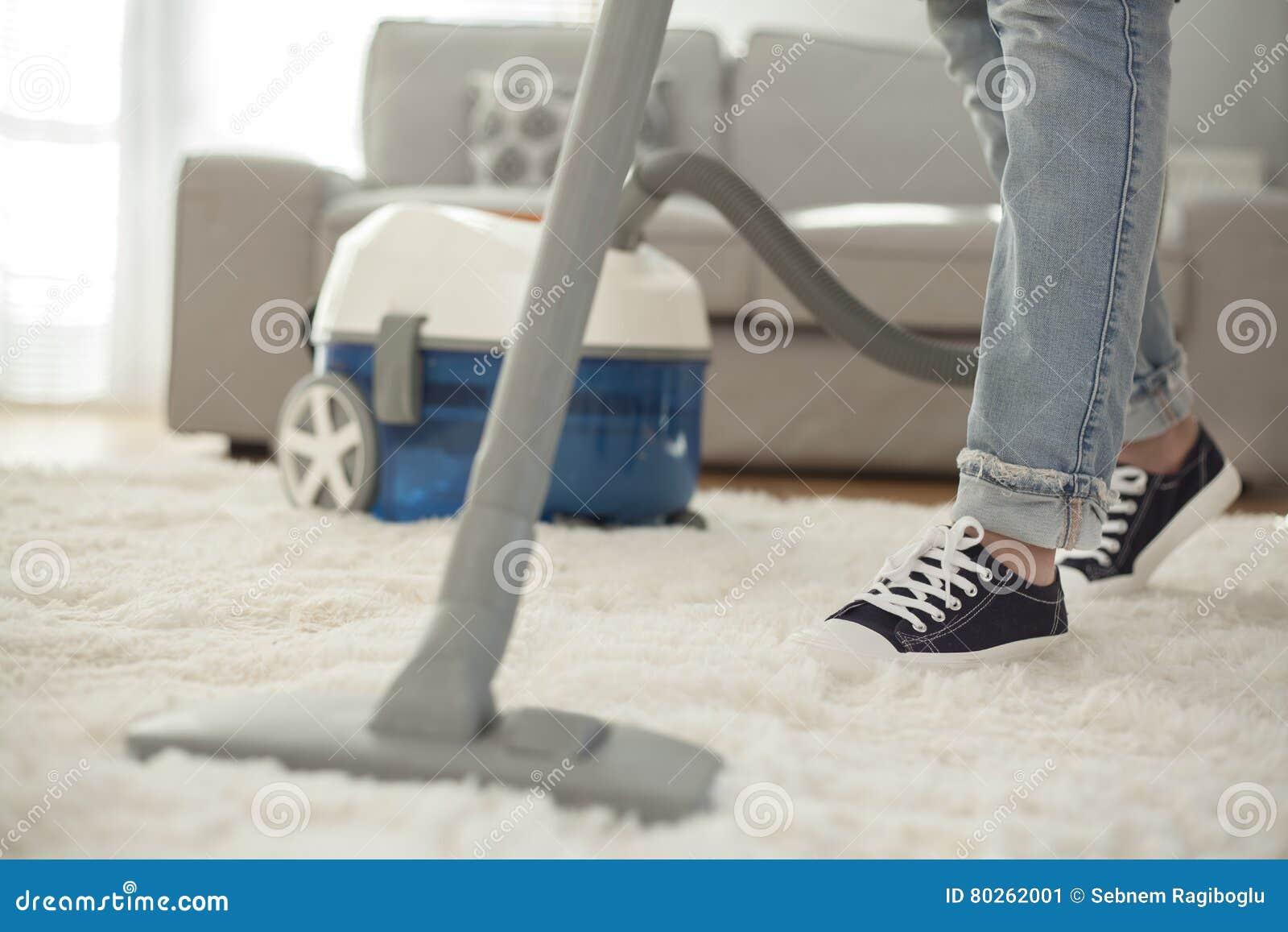 Frauenreinigungsteppich mit einem Staubsauger im Raum