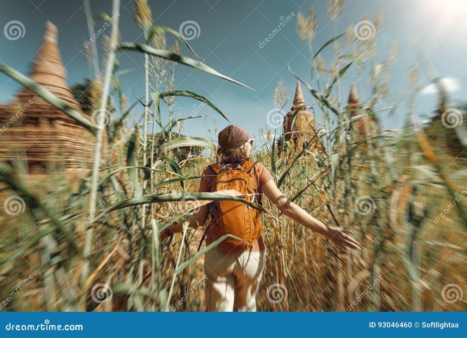 Frauenreisender mit einem Rucksacklauf durch Feld zum alten stup
