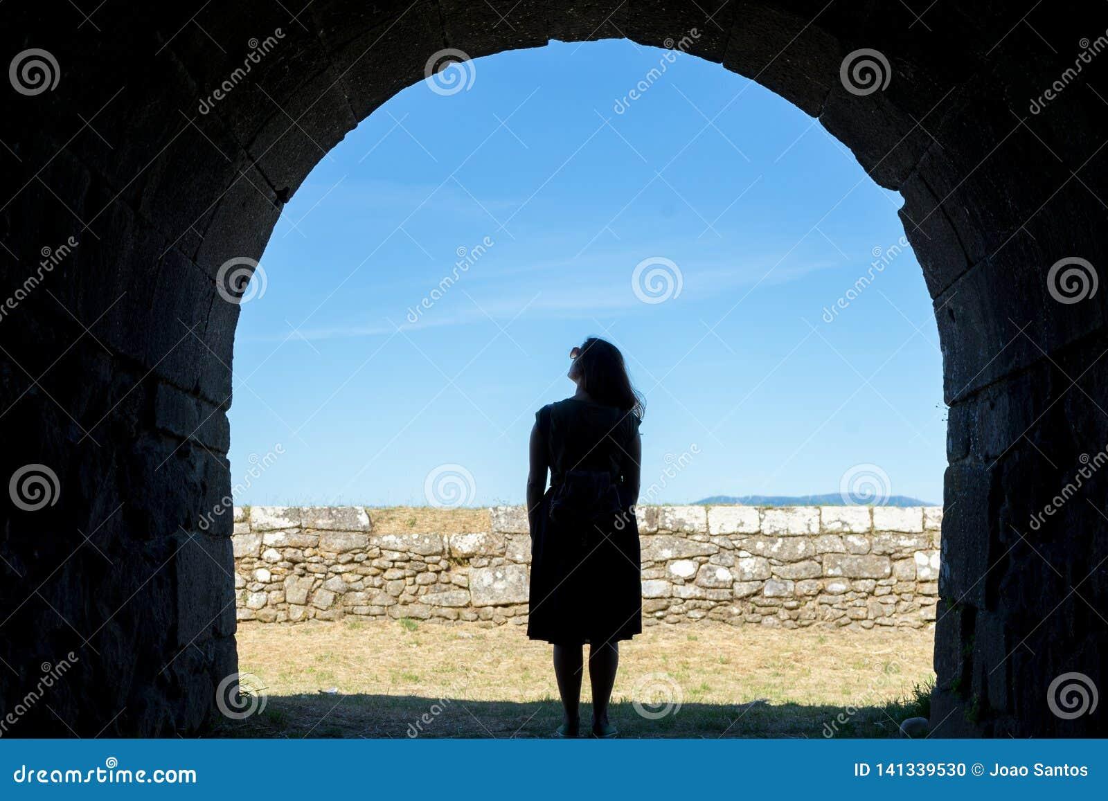 Frauenschattenbild auf einem alten Steintunnel