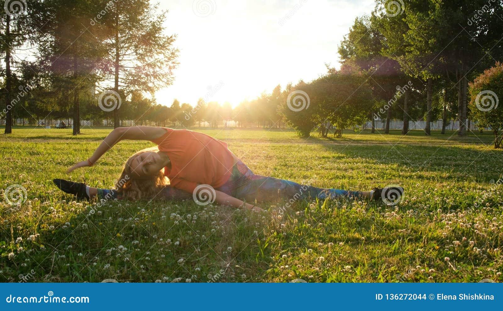 Frauenturner sitzt auf einer Schnur auf dem Gras in einem Stadtpark in der Natur und tut ausdehnend