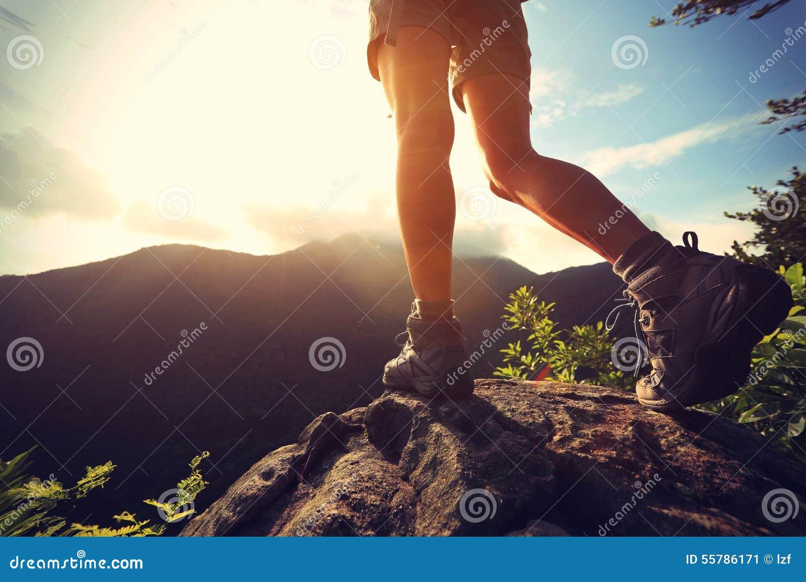 Frauenwanderer, der Stand auf Klippe wandert