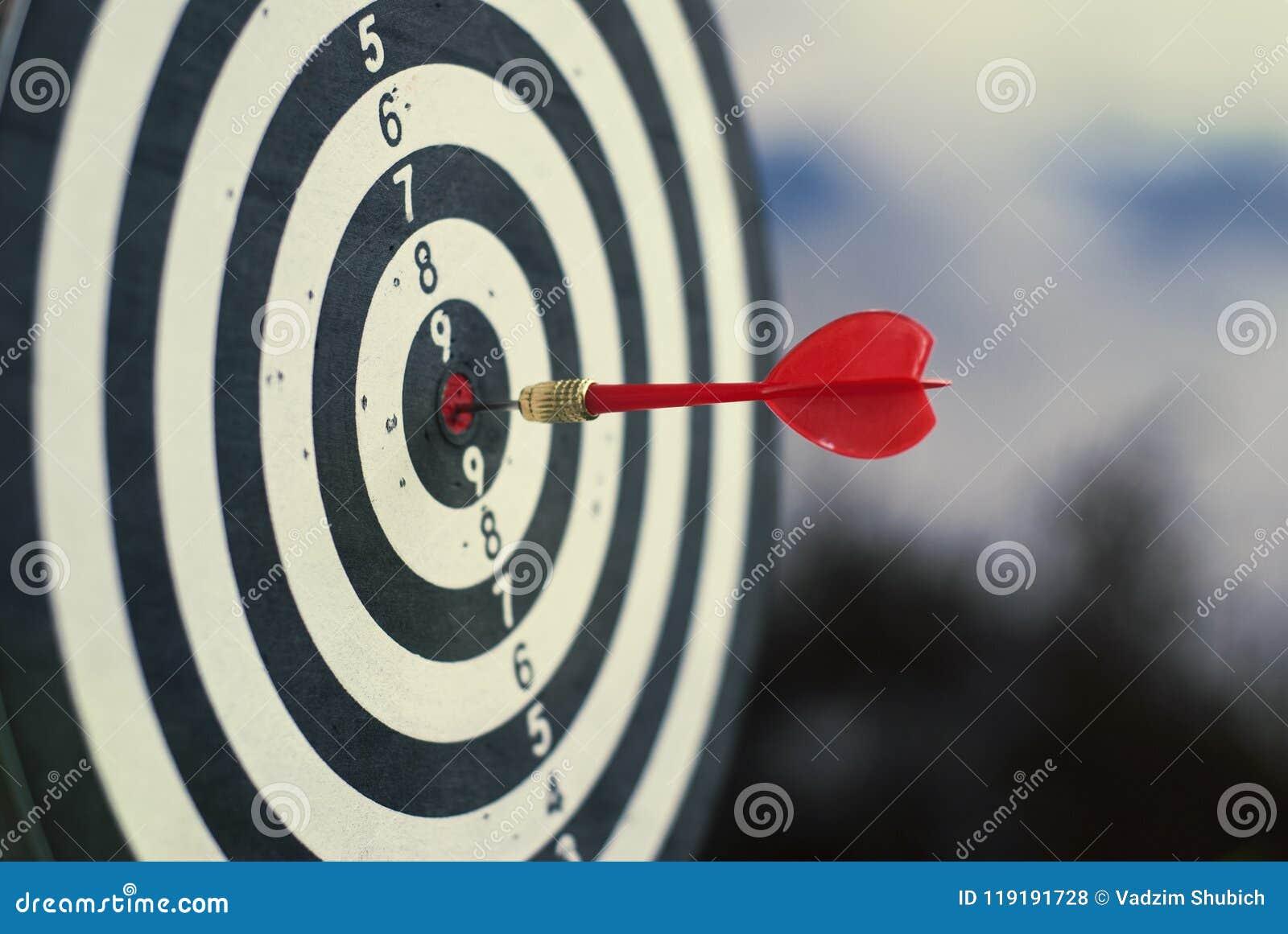 Freccia rossa sparata del dardo nel centro del bersaglio Concetto per mirare al successo ed al vincitore