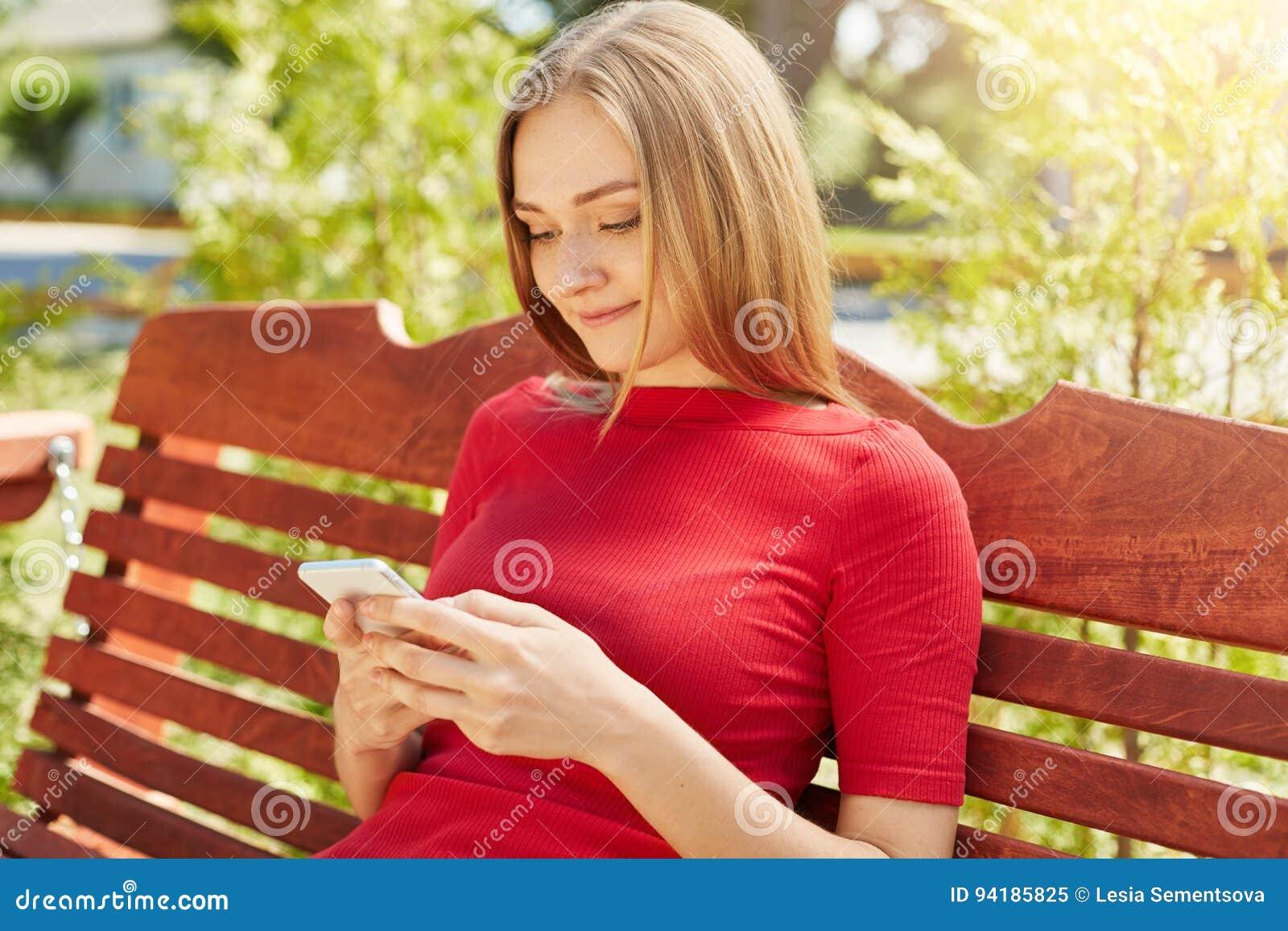 Freckled meisje met recht kapsel die rode kledingszitting in park dragen bij bank die haar celtelefoon met behulp van die sociale