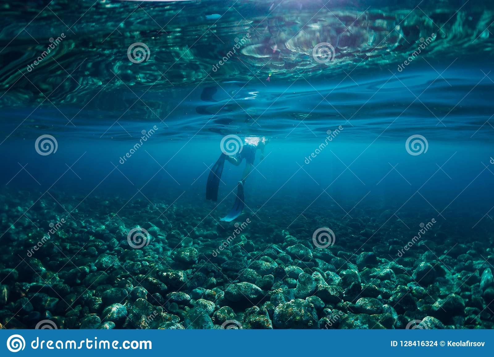 Free diver swim in ocean, underwater photo with sunlight