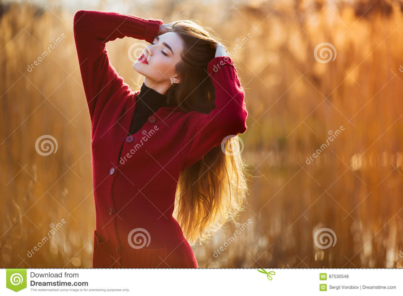 Free happy young woman. Beautiful female with long healthy blowing hair enjoying sun light in park at sunset. Spring
