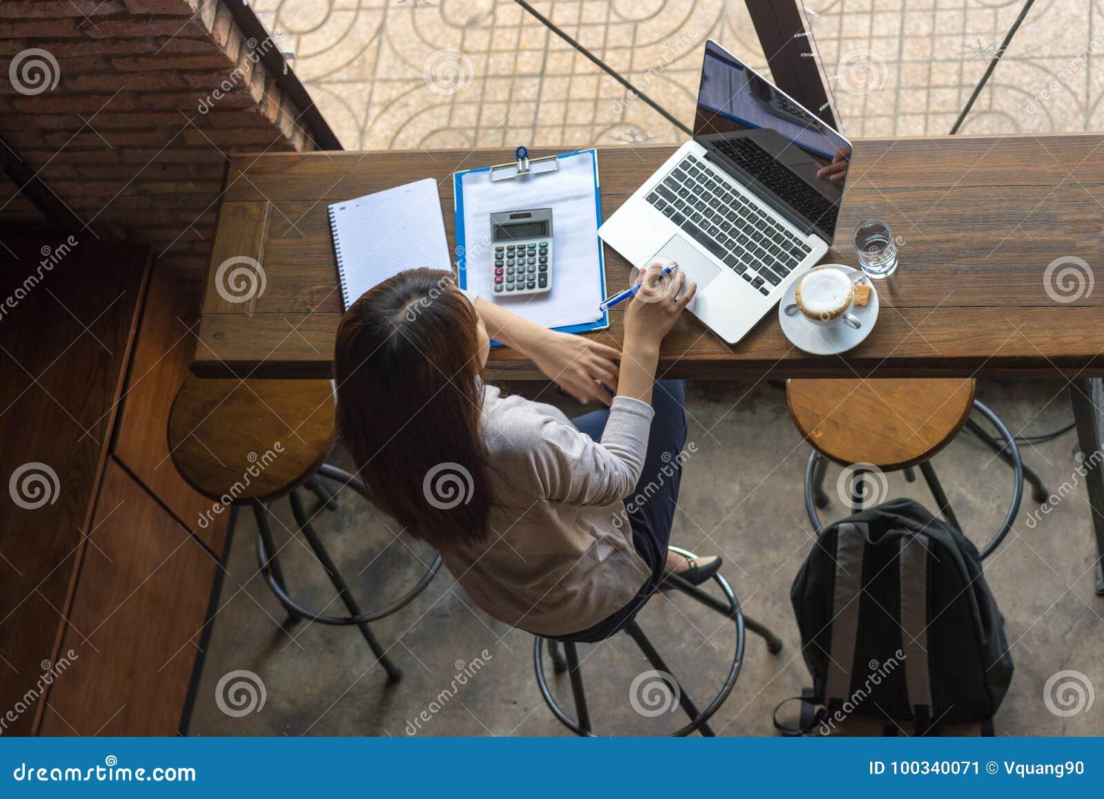 Free lance asiatiche che lavorano al computer portatile al caffè