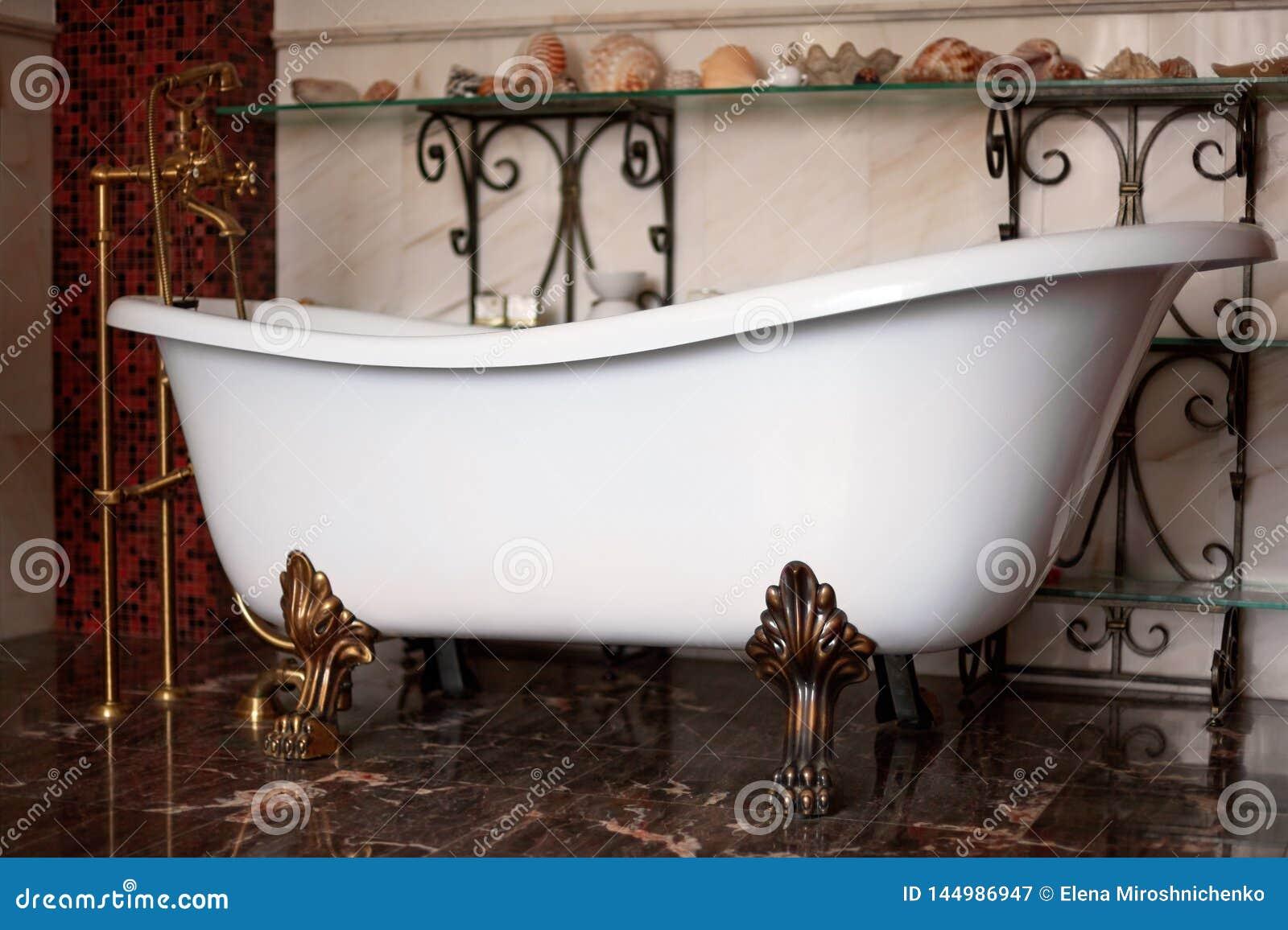 Free-standing bathtube van het luxe uitstekende brons clawfoot in uitstekend binnenland Donkere warme kleurenachtergrond met shel