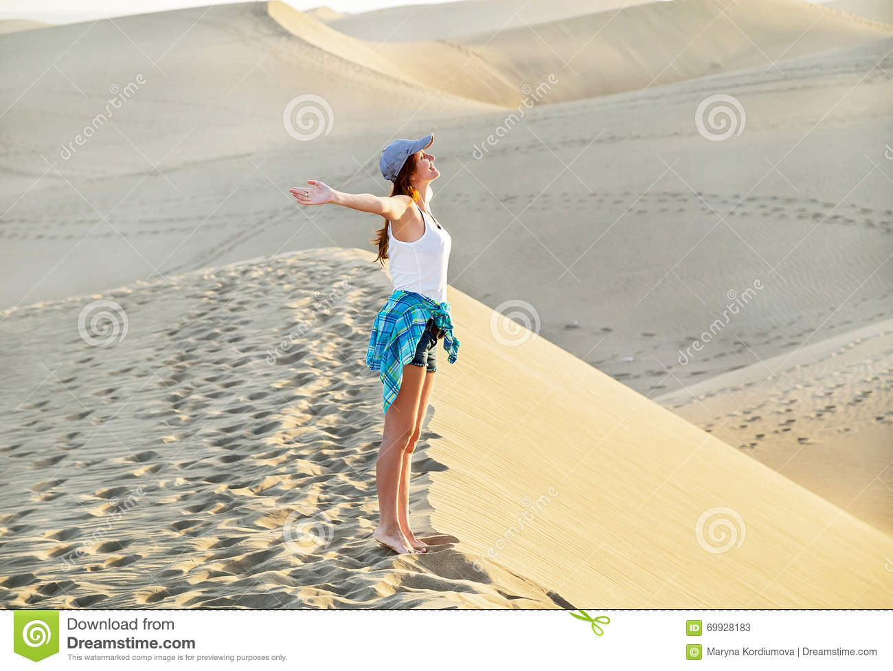 Free young woman in Maspalomas beach. Inspirational sandy dunes on sunny summer day. Gran Canaria, Spain.