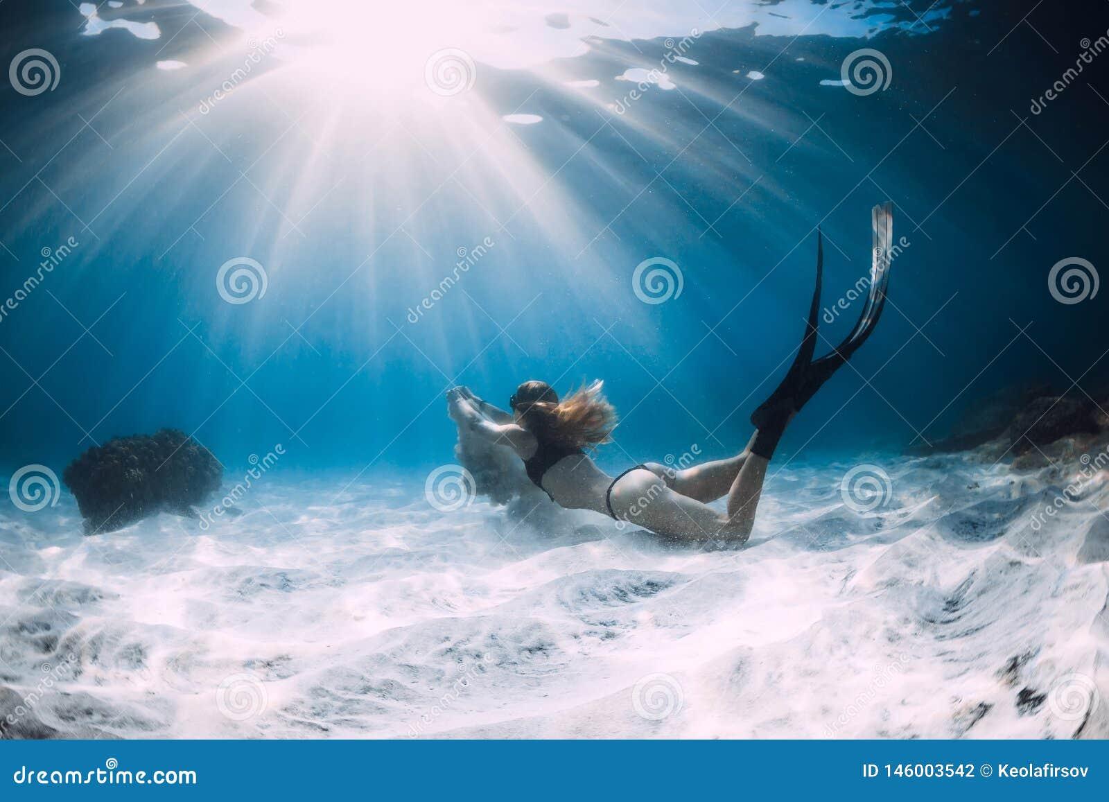 Freediver della donna con la sabbia bianca sopra il mare sabbioso con le alette Freediving subacqueo