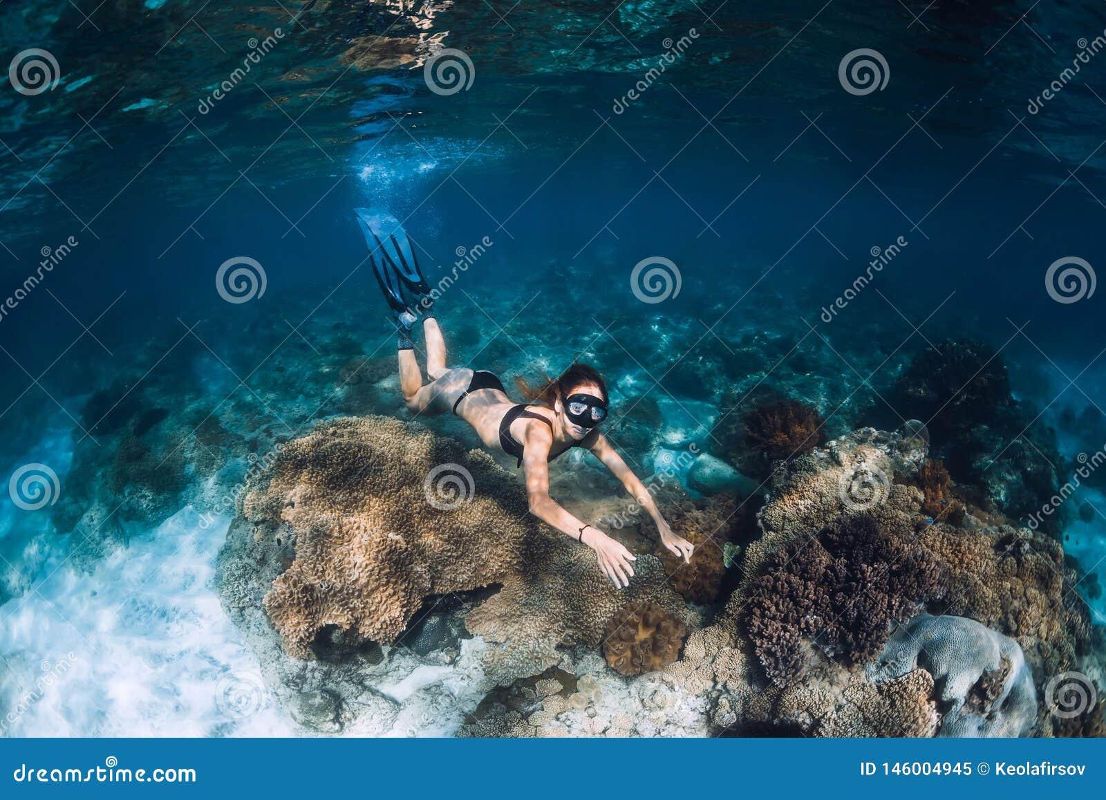 Freediver della donna con le alette ed i coralli Freediving subacqueo in oceano