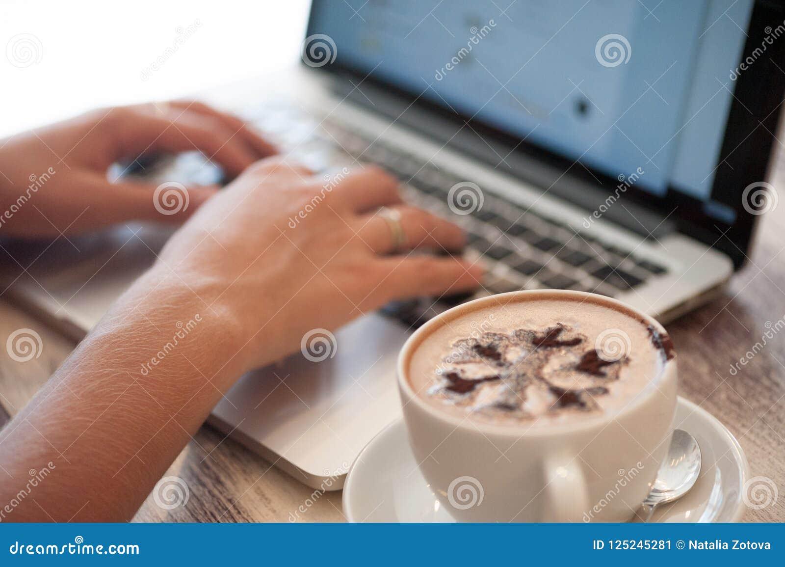 Freelancer da jovem mulher que datilografa no portátil no café