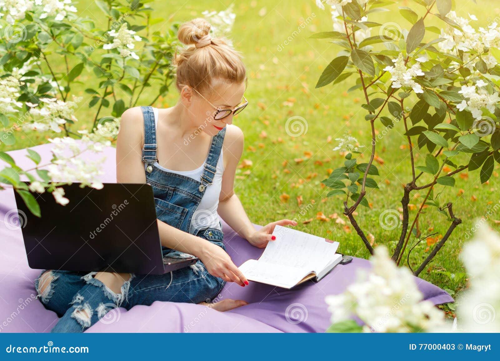 Freelancer die in de tuin werken Schrijven, die in Internet surfen Jonge vrouw die en pret op parkgebied ontspannen hebben die co
