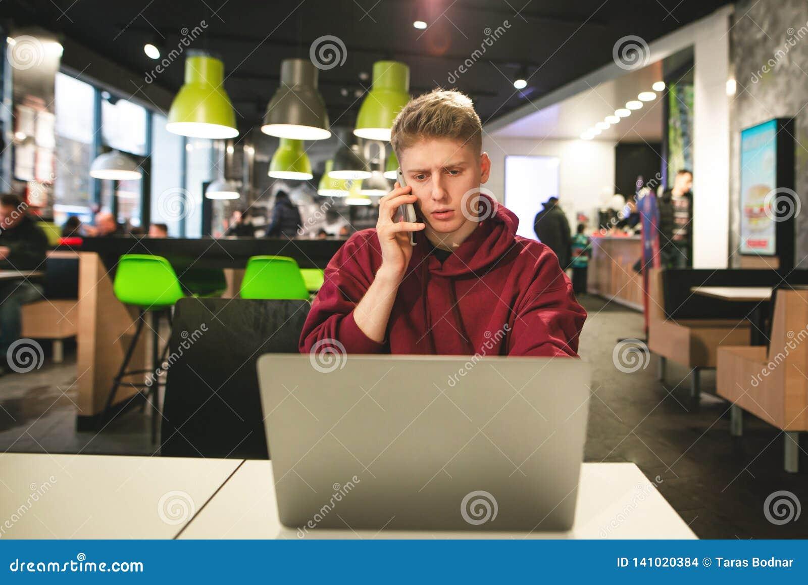Freelancer pracuje na laptopie w kawiarni i dzwoni telefon Biznesowy młodego człowieka obsiadanie z laptopem w fast food kawiarni