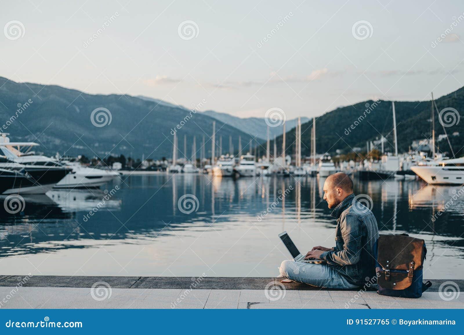 Freelancer que trabaja en el ordenador portátil en la orilla cerca del barco del yate en