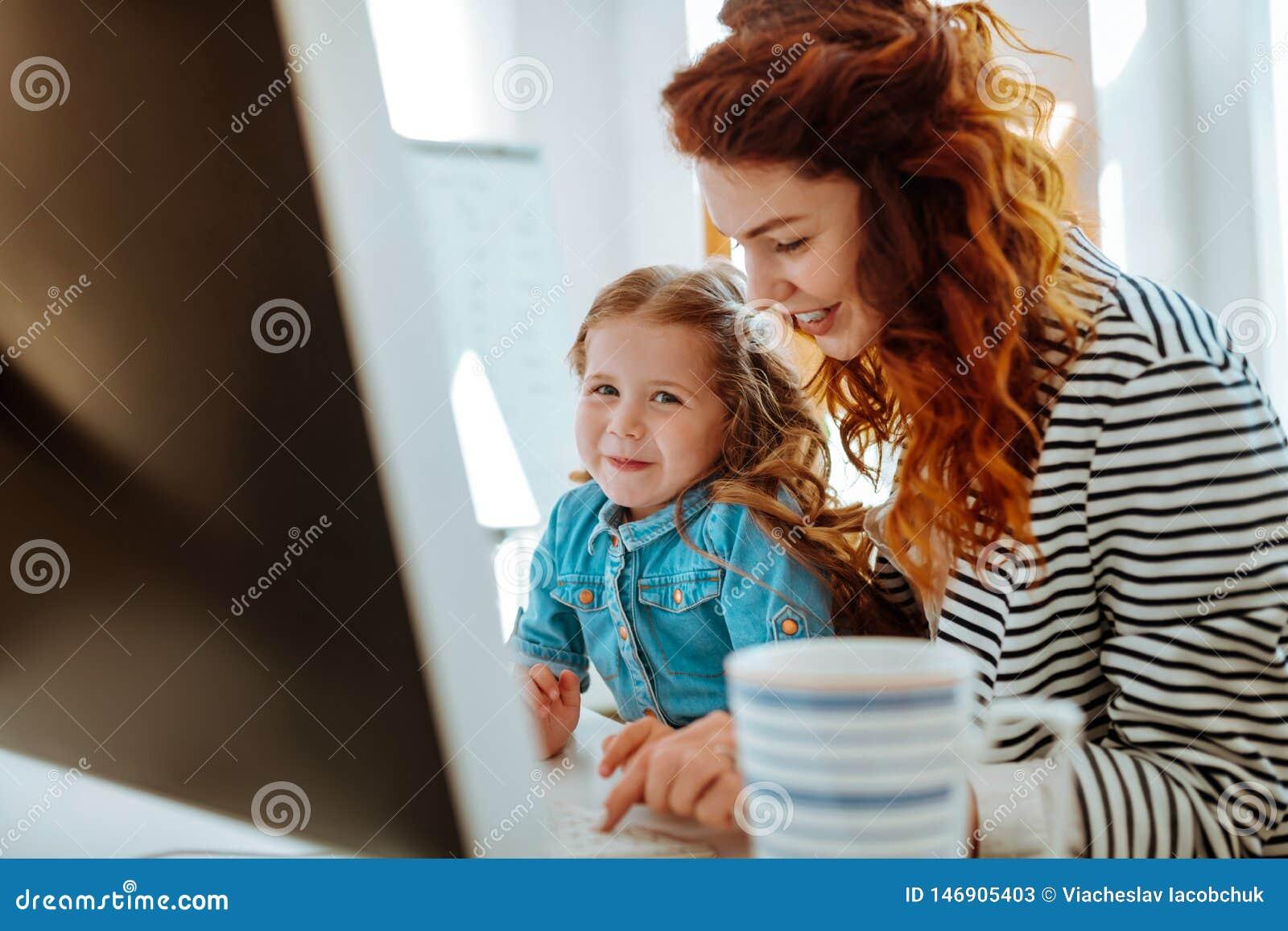 Freelancer som ler stund som arbetar nära hennes älskvärda dotter