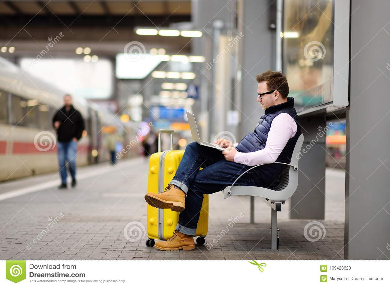 Freelancer working with a laptop in a train station while is waiting for transport
