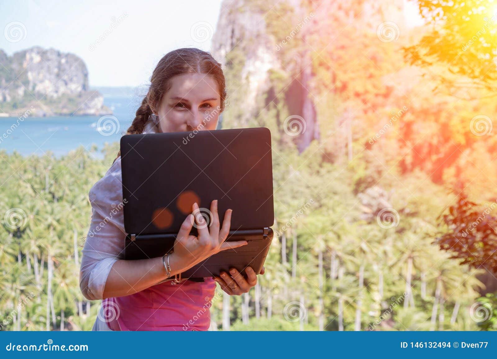 Freelancerflicka som döljer bak en bärbar datorskärm Hon står på kanten av vaggar med dess baksida till havet och den tropiska sk