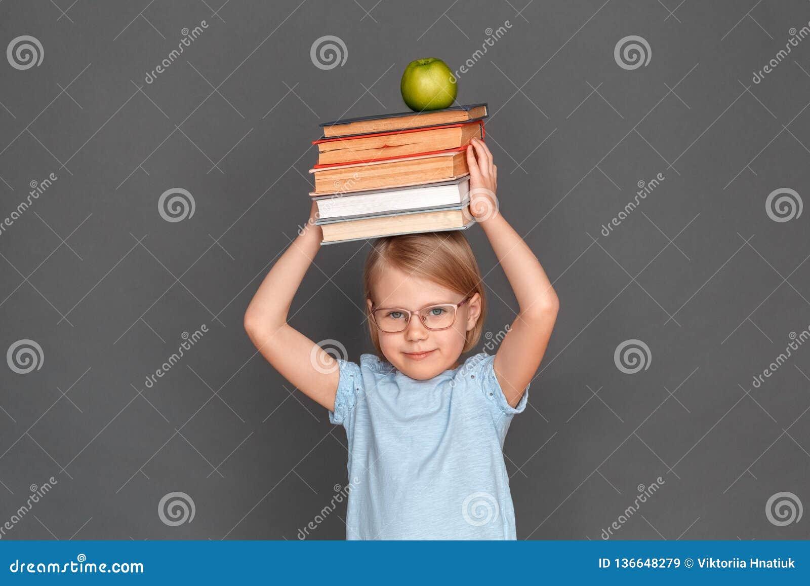 Freestyle Μικρό κορίτσι eyeglasses που απομονώνεται στο γκρι με τα βιβλία και το μήλο επάνω από το επικεφαλής χαμόγελο χαρούμενο