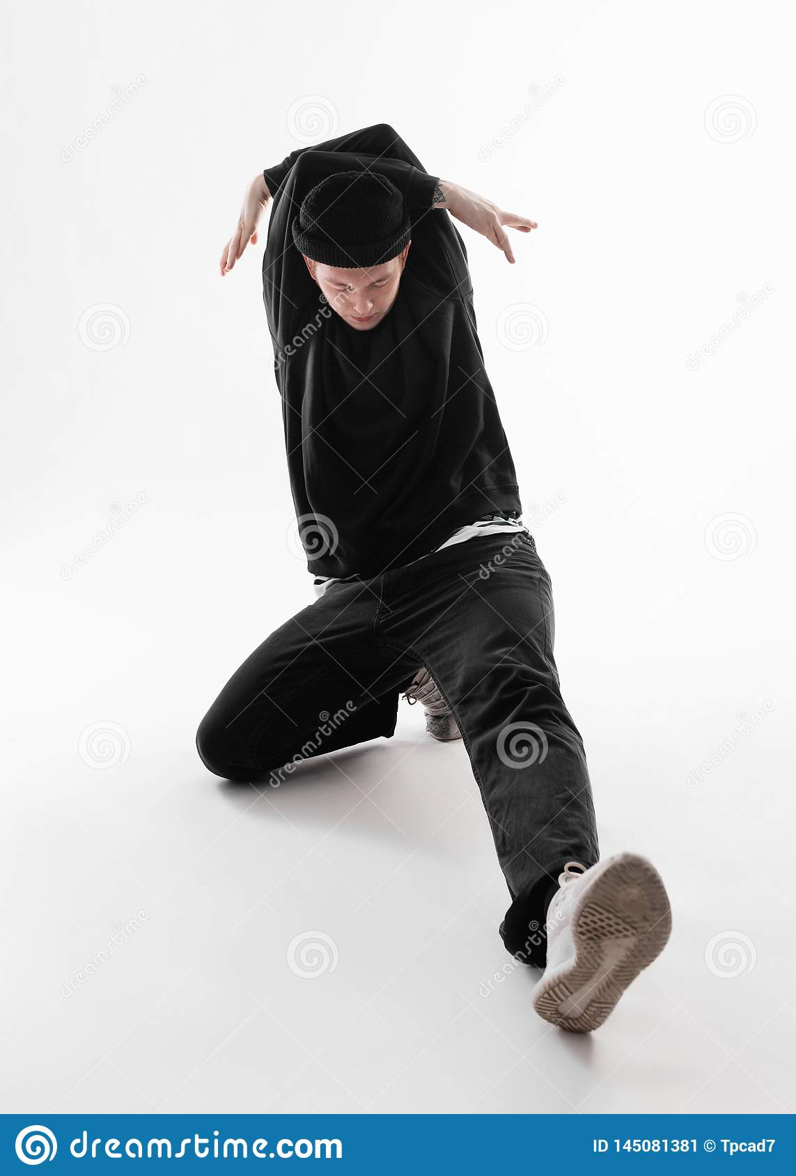 Freestyle dancer dressed in black jeans, sweatshirt, hat and gray sneakers is dancing squatting in the studio on the