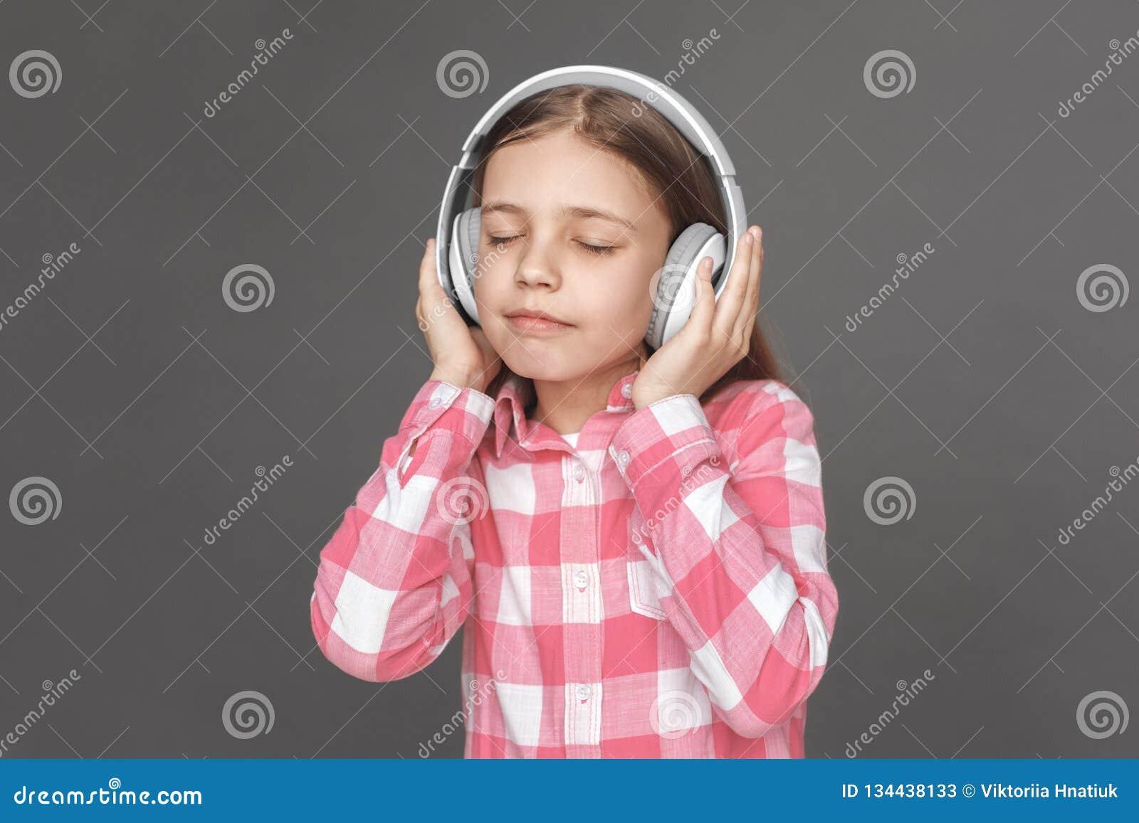 Freestyle Dziewczyna w hełmofonów stać odizolowywam na popielatym słuchaniu muzyka zamykająca przygląda się radosnego w górę