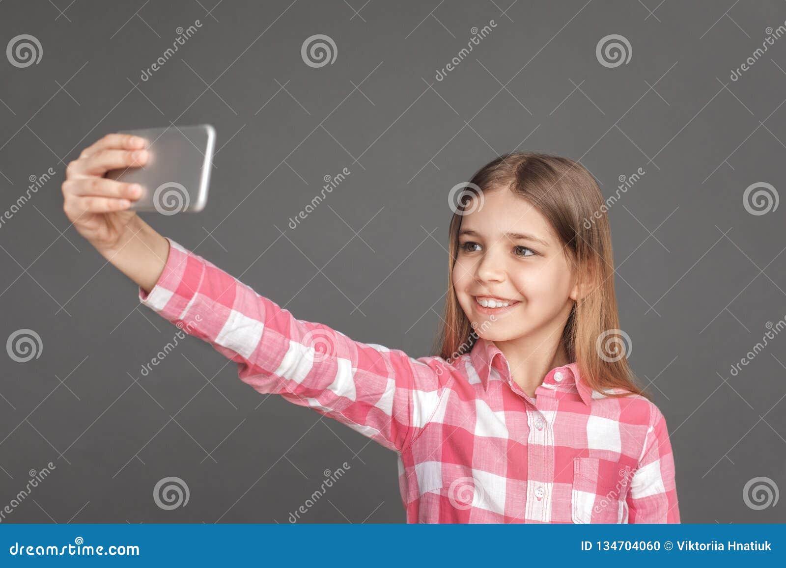 Freestyle Dziewczyny pozycja odizolowywająca na popielatym bierze selfie na smartphone przyglądającej kamerze rozochoconej