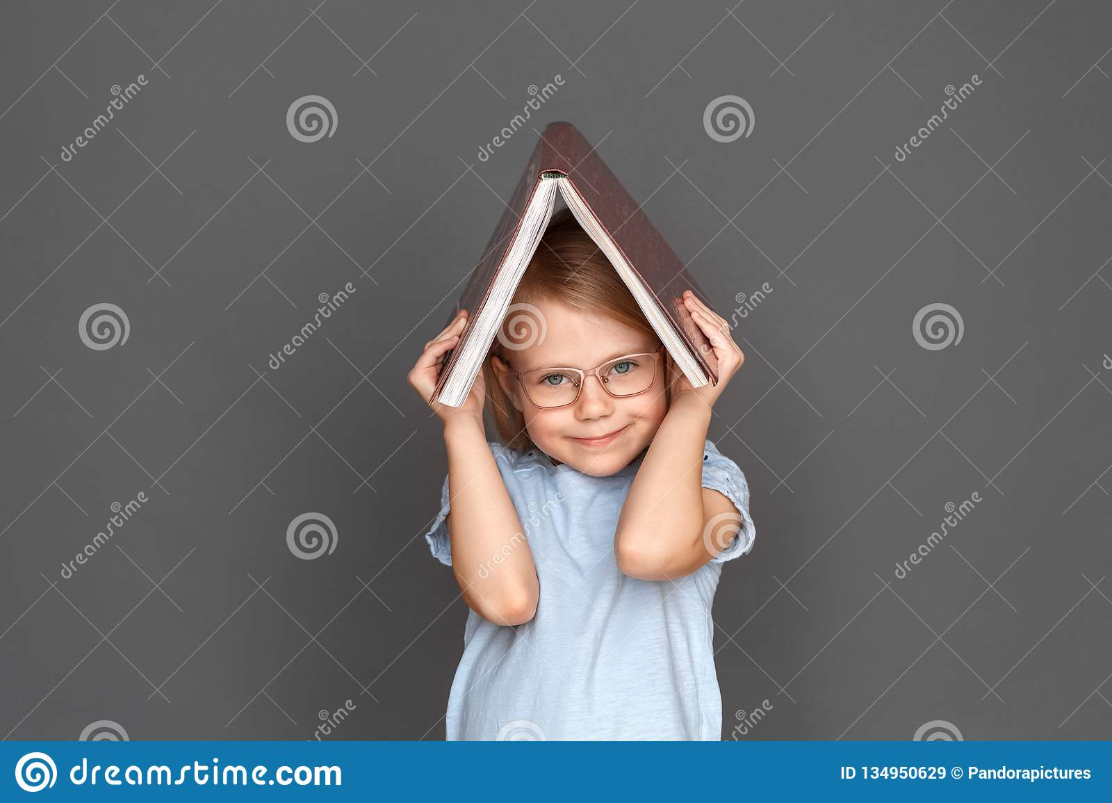 Freestyle. Little girl in eyeglasses on grey hiding under book smiling cute