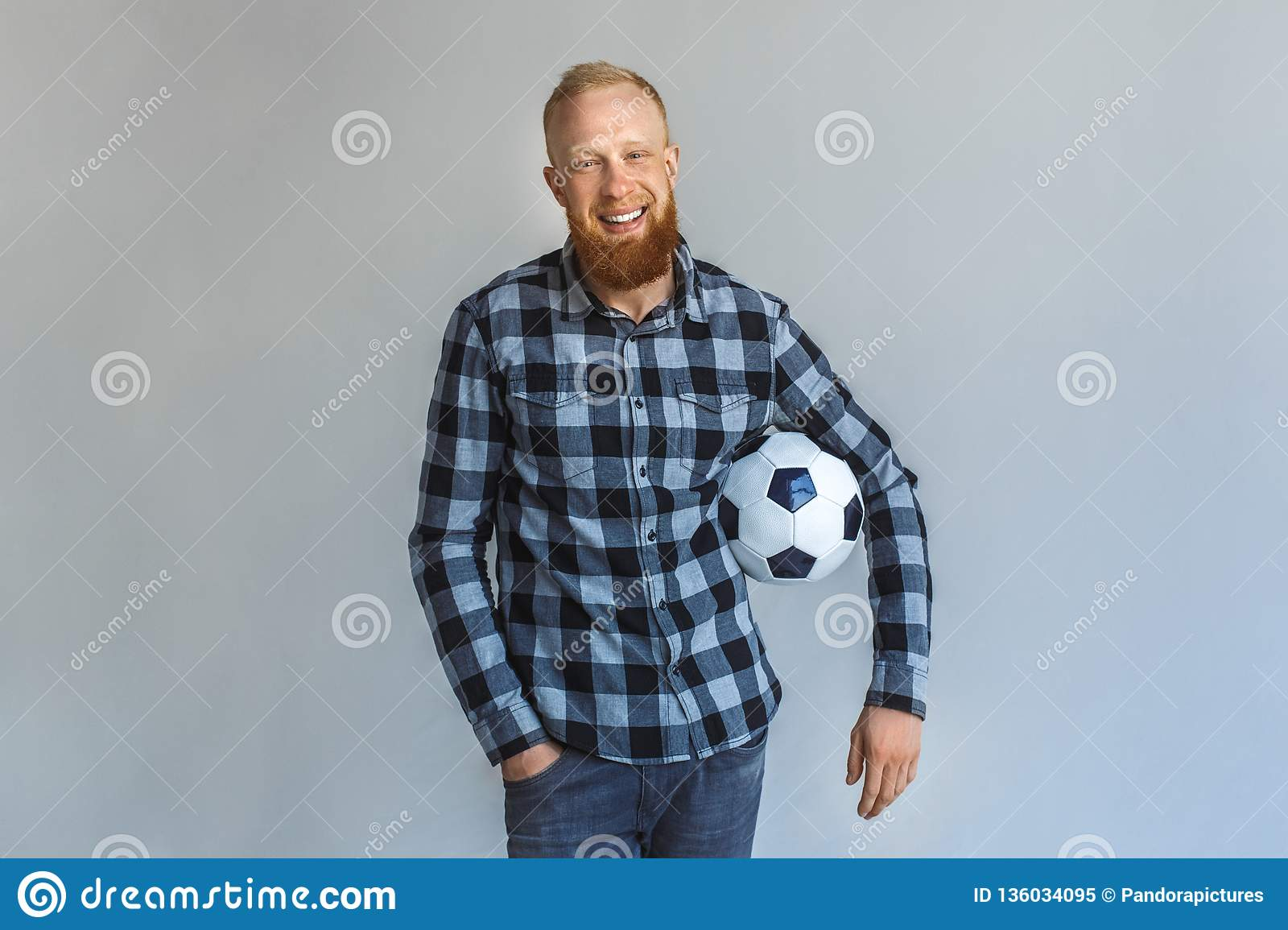 Freestyle. Mature man standing isolated on grey with ball smiling relaxed