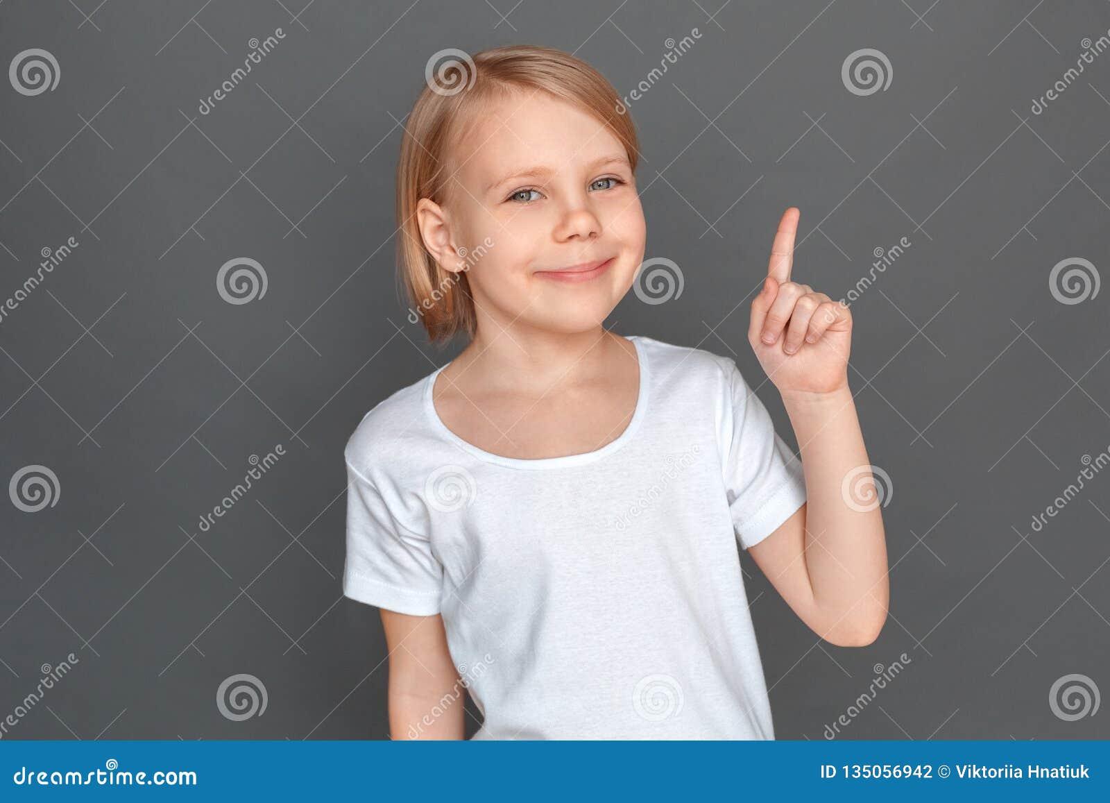 Freestyle Meisje op grijs wordt geïsoleerd die op ruimteterloopse opmerking richten die blij close-up glimlachen dat