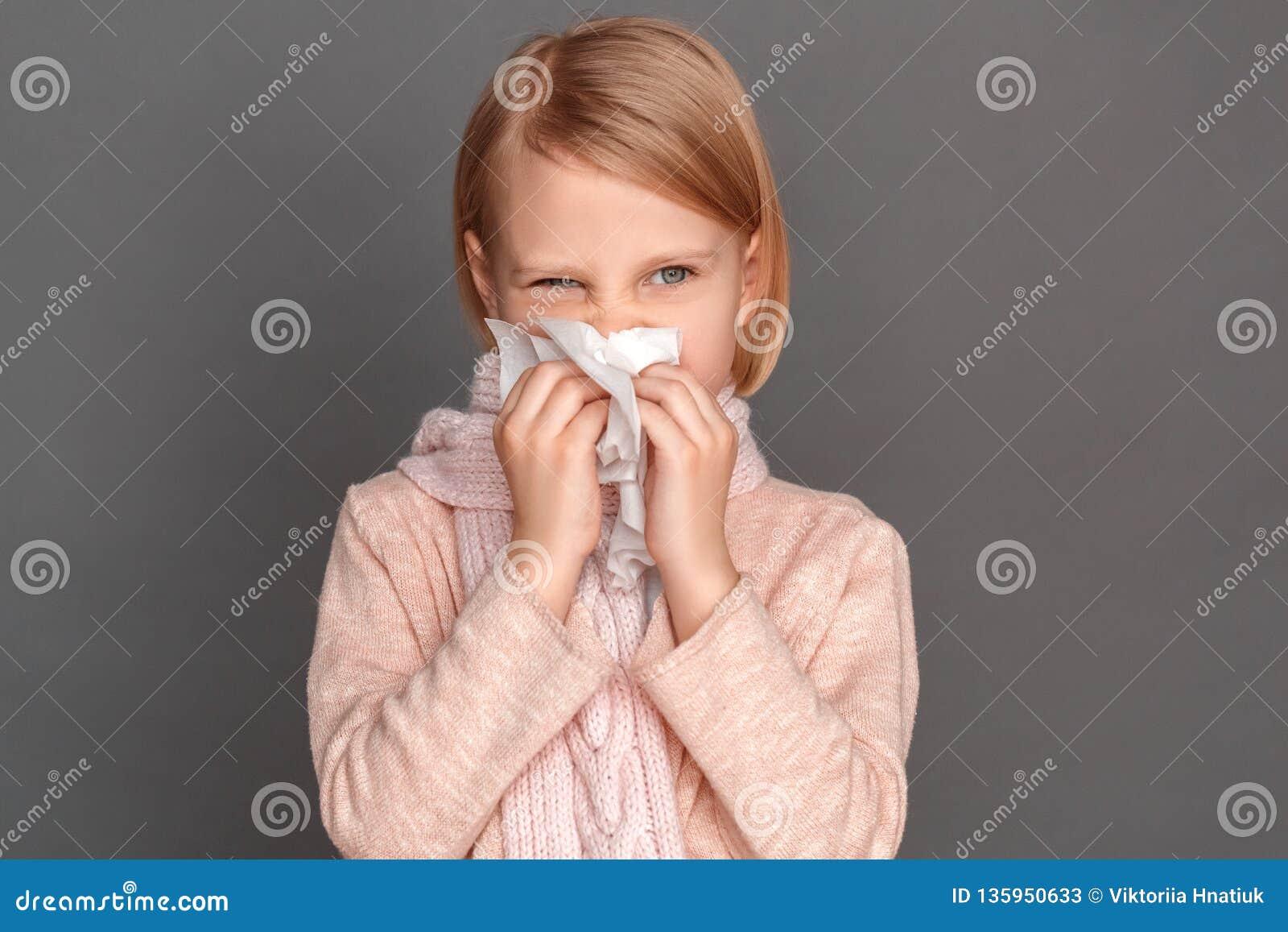 Freestyle Menina no lenço isolado no nariz de sopro cinzento no tecido que olha de lado close-up interessado