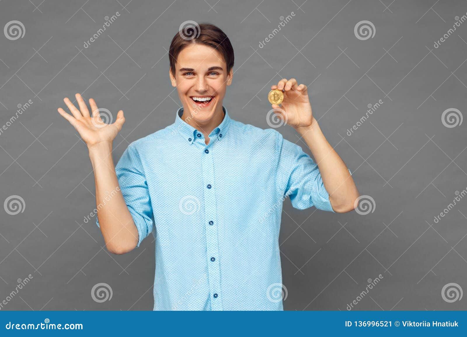 Freestyle Nastolatek chłopiec pozycja na popielatym z cryptocurrency gestykuluje ekspresyjny ono uśmiecha się rozochocony