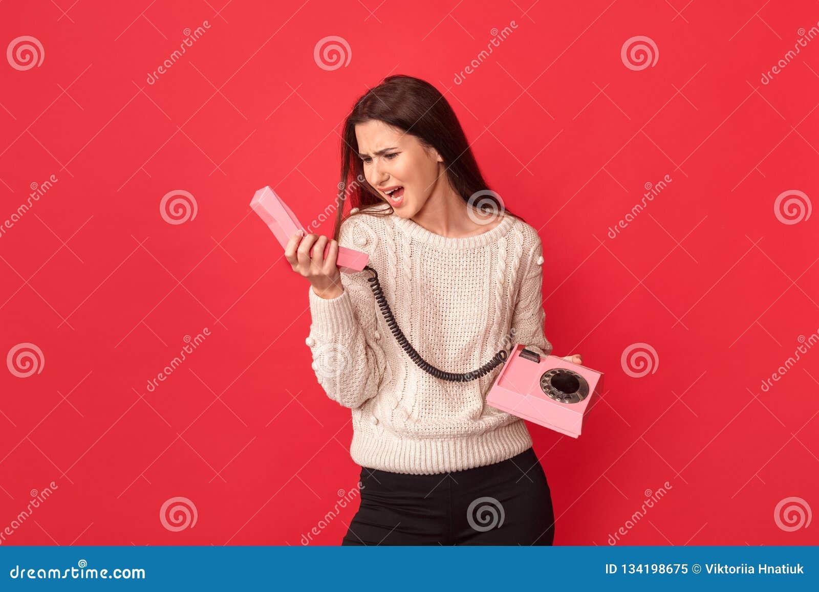 Freestyle Posição da jovem mulher isolada no vermelho com o telefone estacionário que grita para ajustar irritado