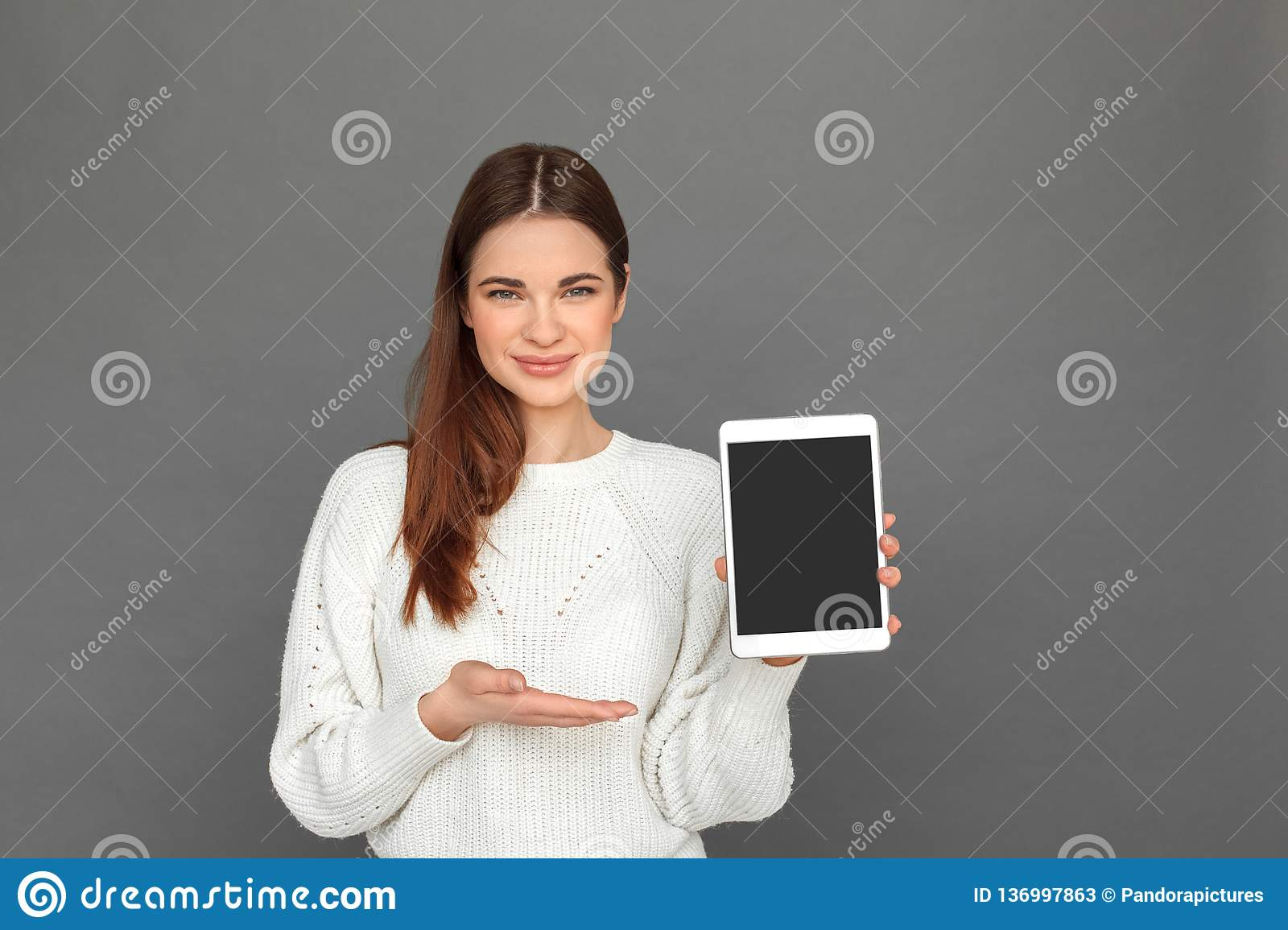 Freestyle. Young girl standing on grey showing screen of digital tablet smiling friendly