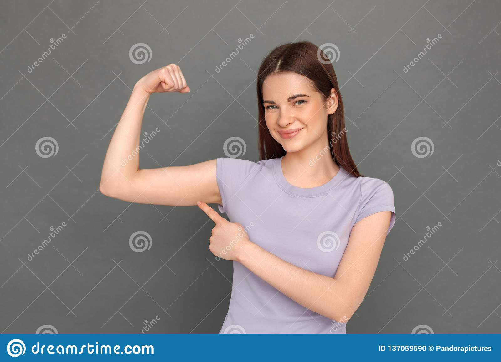 Freestyle. Young girl standing isolated on grey showing arm muscle smiling confident close-up