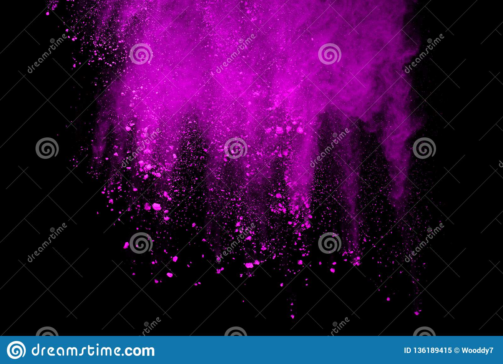 Freeze motion of purple powder exploding on black background.