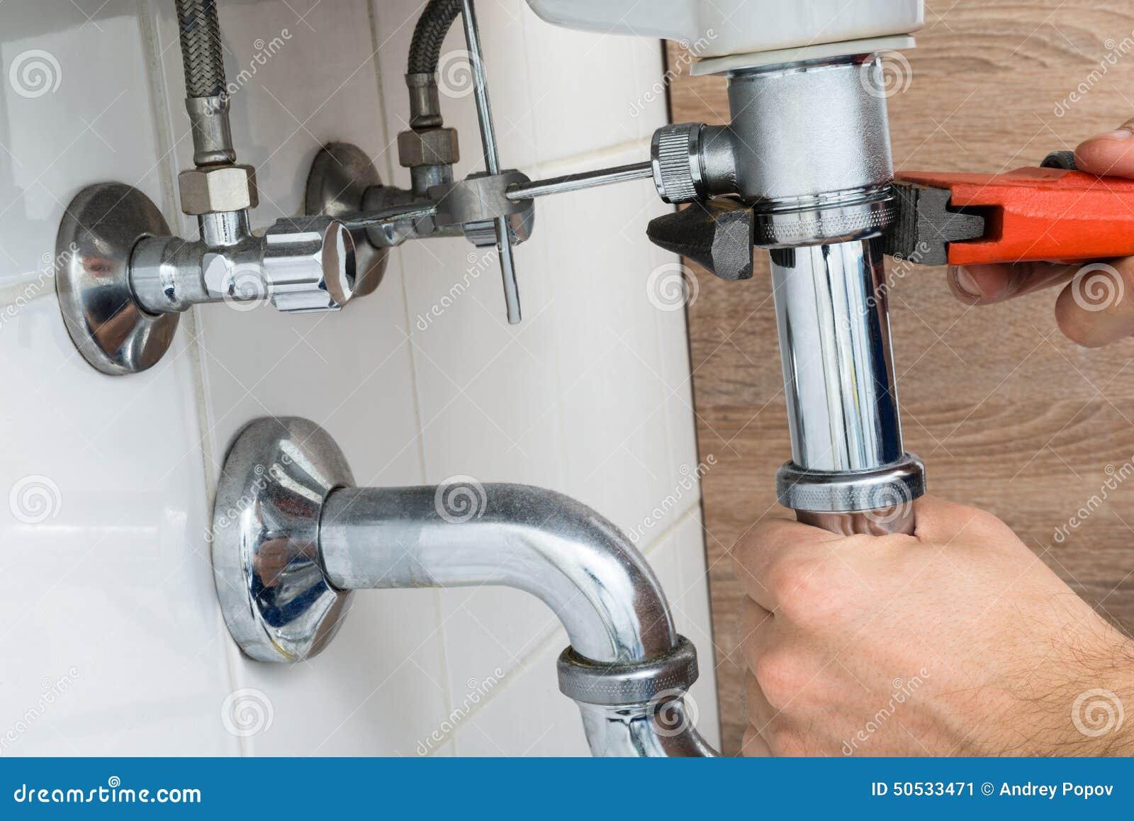 Fregadero masculino de la fijación del fontanero en cuarto de baño
