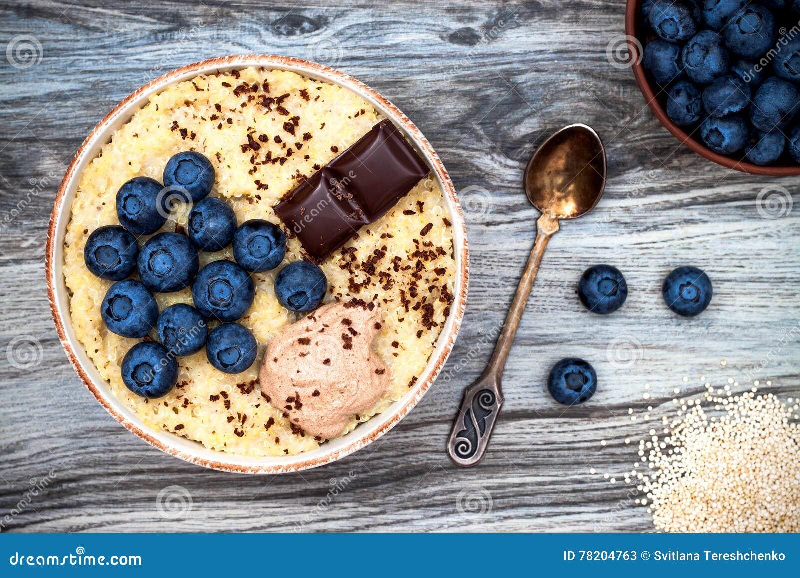 Freier Amarant des Glutens und Quinoabreifrühstück rollen mit Blaubeeren und Schokolade über rustikalem hölzernem Hintergrund