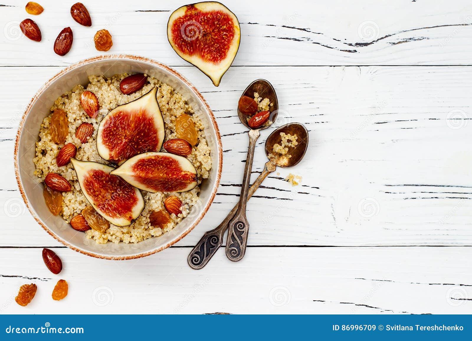 Freier Amarant des Glutens und Quinoabreifrühstück rollen mit Feigen, karamellisierten Mandeln, Rosinen und Honig über rustikaler