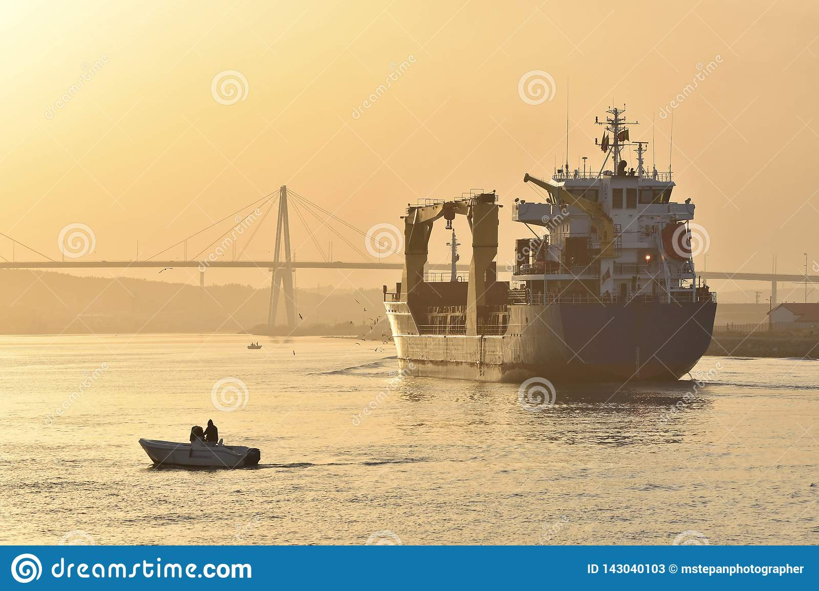Freight ship in morning mist on river Mondego Portugal