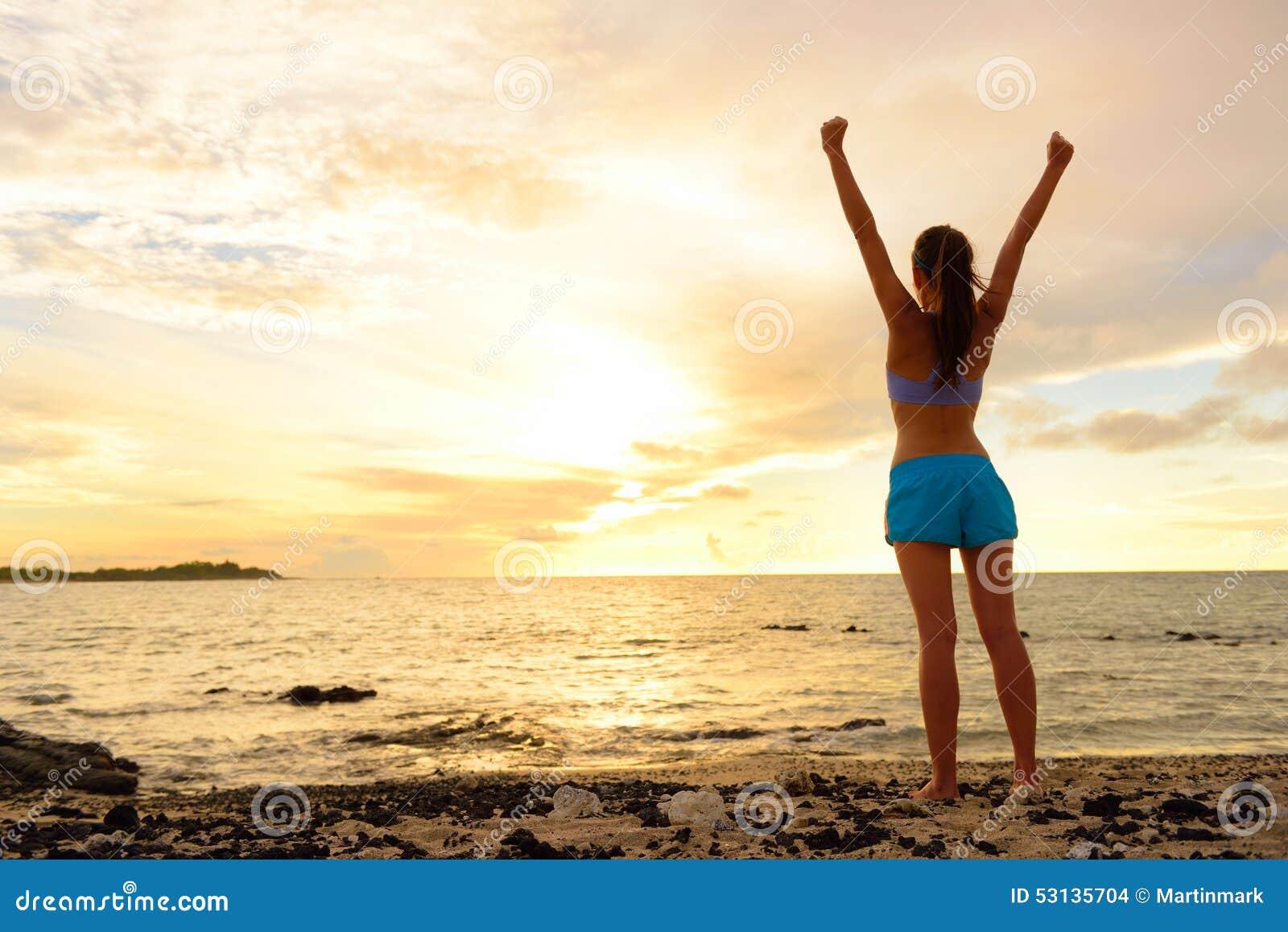 Freiheitserfolgsfrau, die am Sonnenuntergangstrand zujubelt