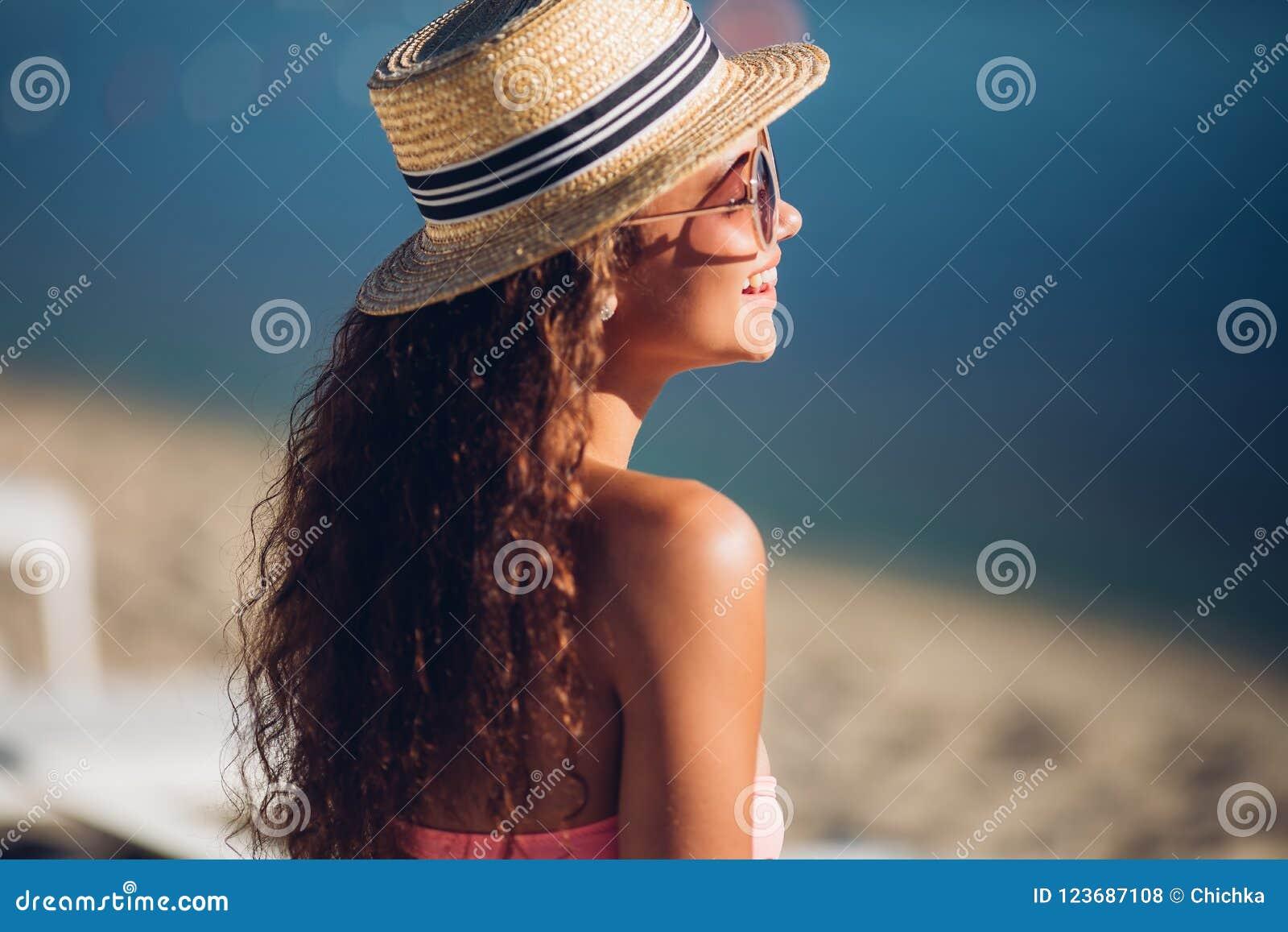 Freiheitsfrau lachend, kühlen Sie Hippie-Mädchen im Sommerstrohhut ab, der neben heißem Sommermode-accessoire des exotischen Somm