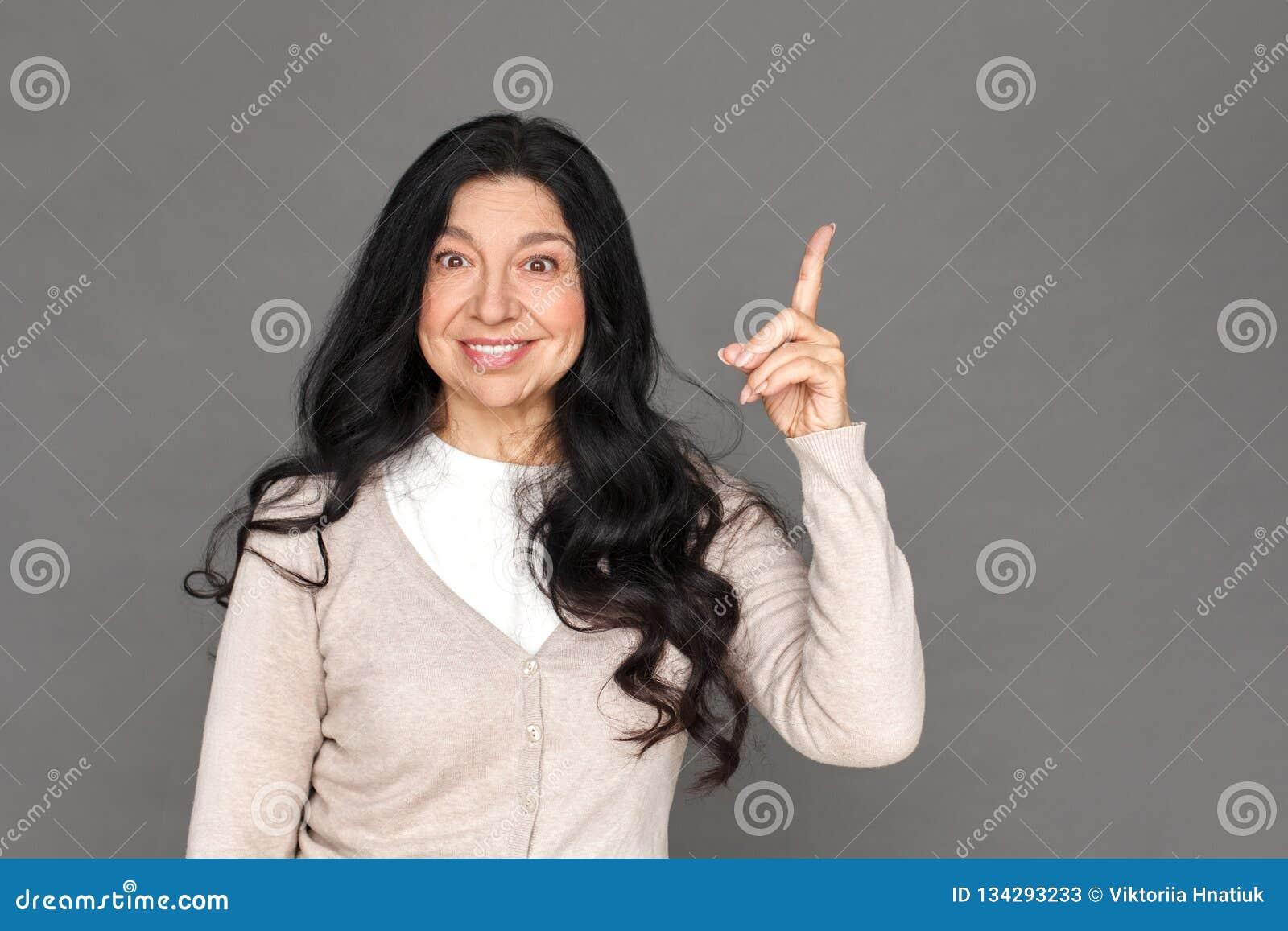 Freistil Reife Damenstellung lokalisiert auf dem grauem Zeigen herauf das Schauen der Kamera aufgeregt