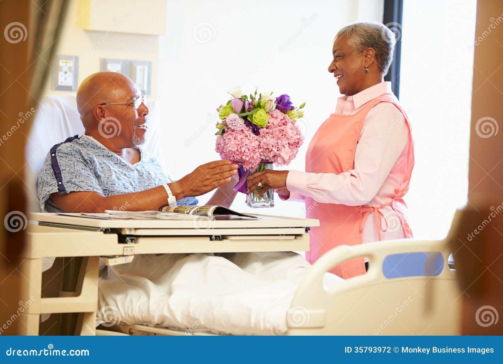 Freiwillige Arbeitskraft, die das Krankenhauszimmer des männlichen Patienten ordnet