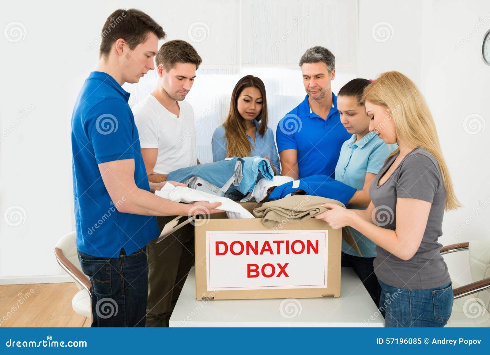 Freiwillige, die Kleidung halten, um zu spenden