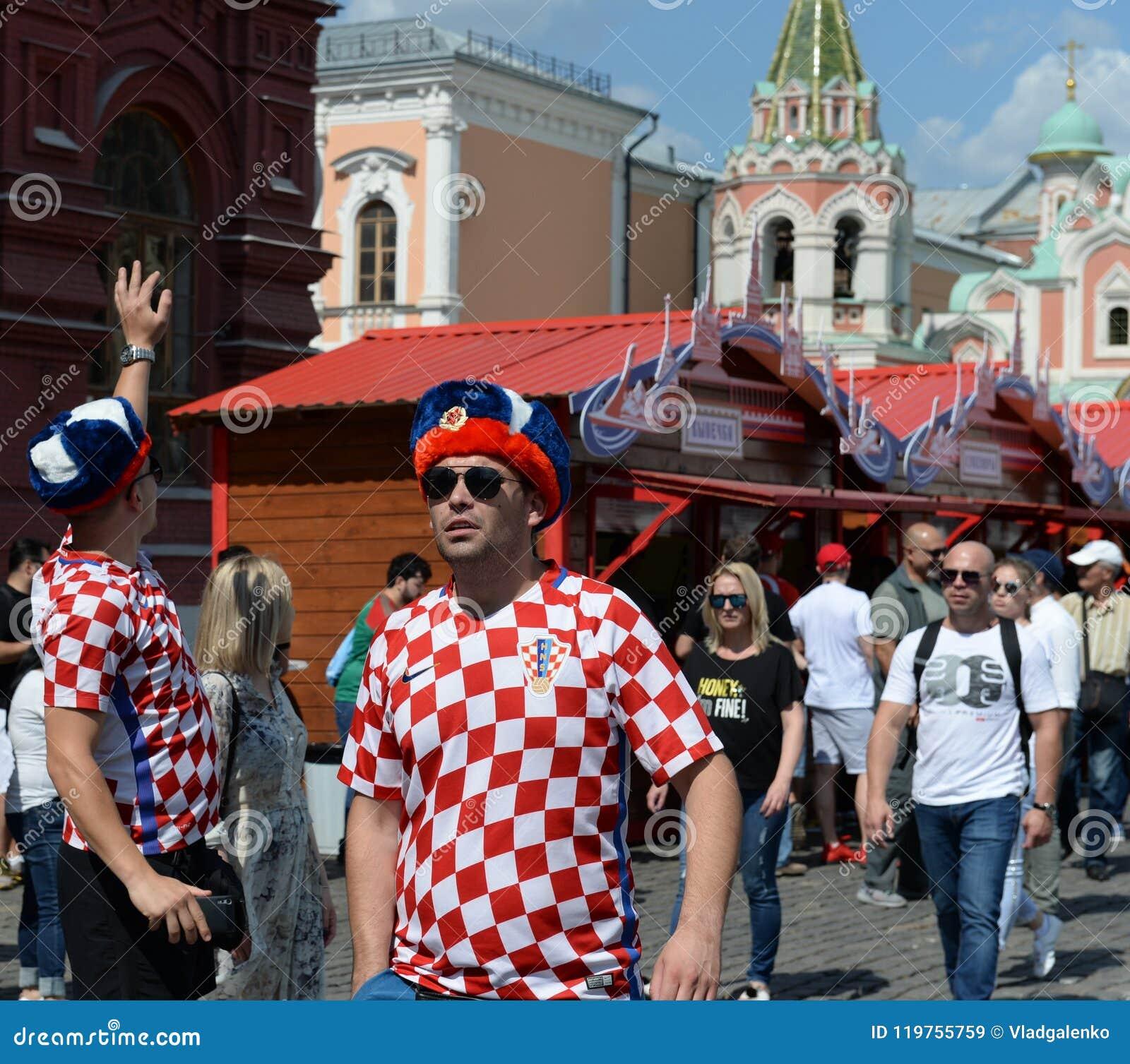 Fremde Fußballfane in den russischen Andenkenhüten auf Rotem Platz