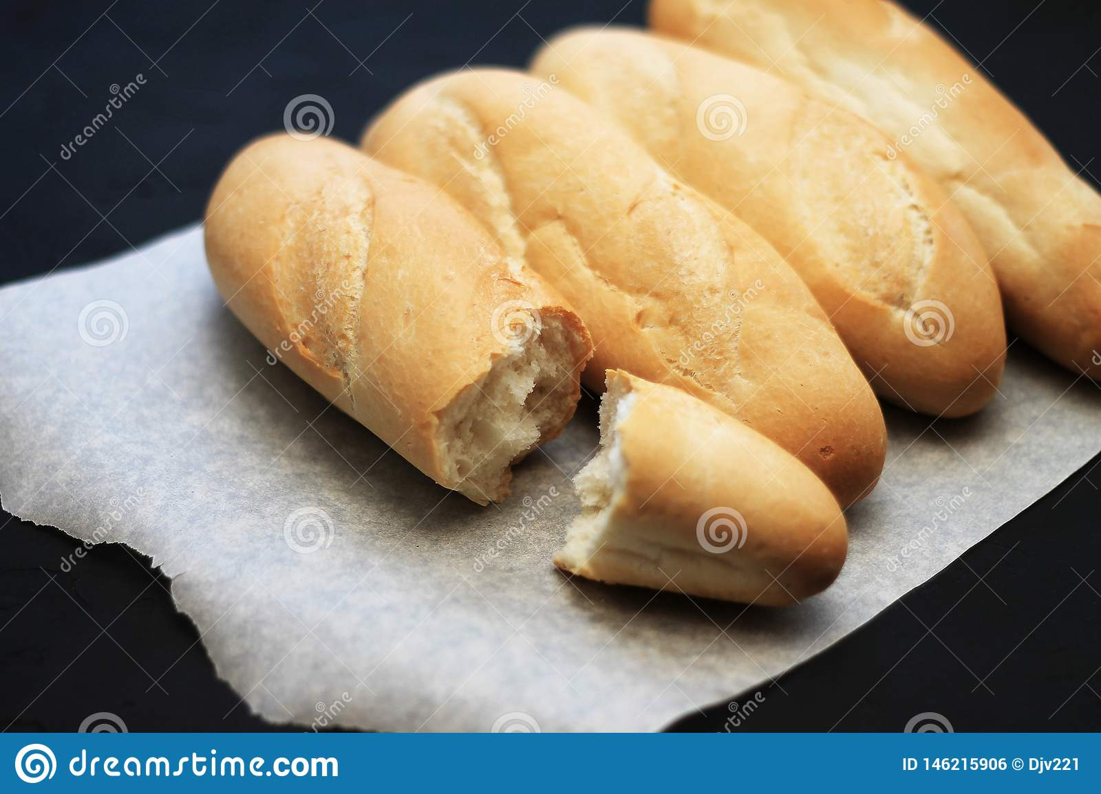 French baguettes, loaves on a black wooden background