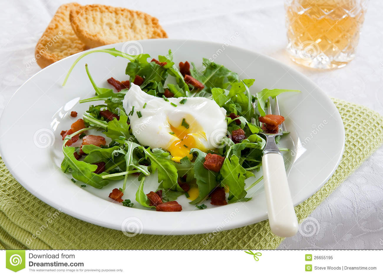 green French bistro style salad on a white plate and table setting.